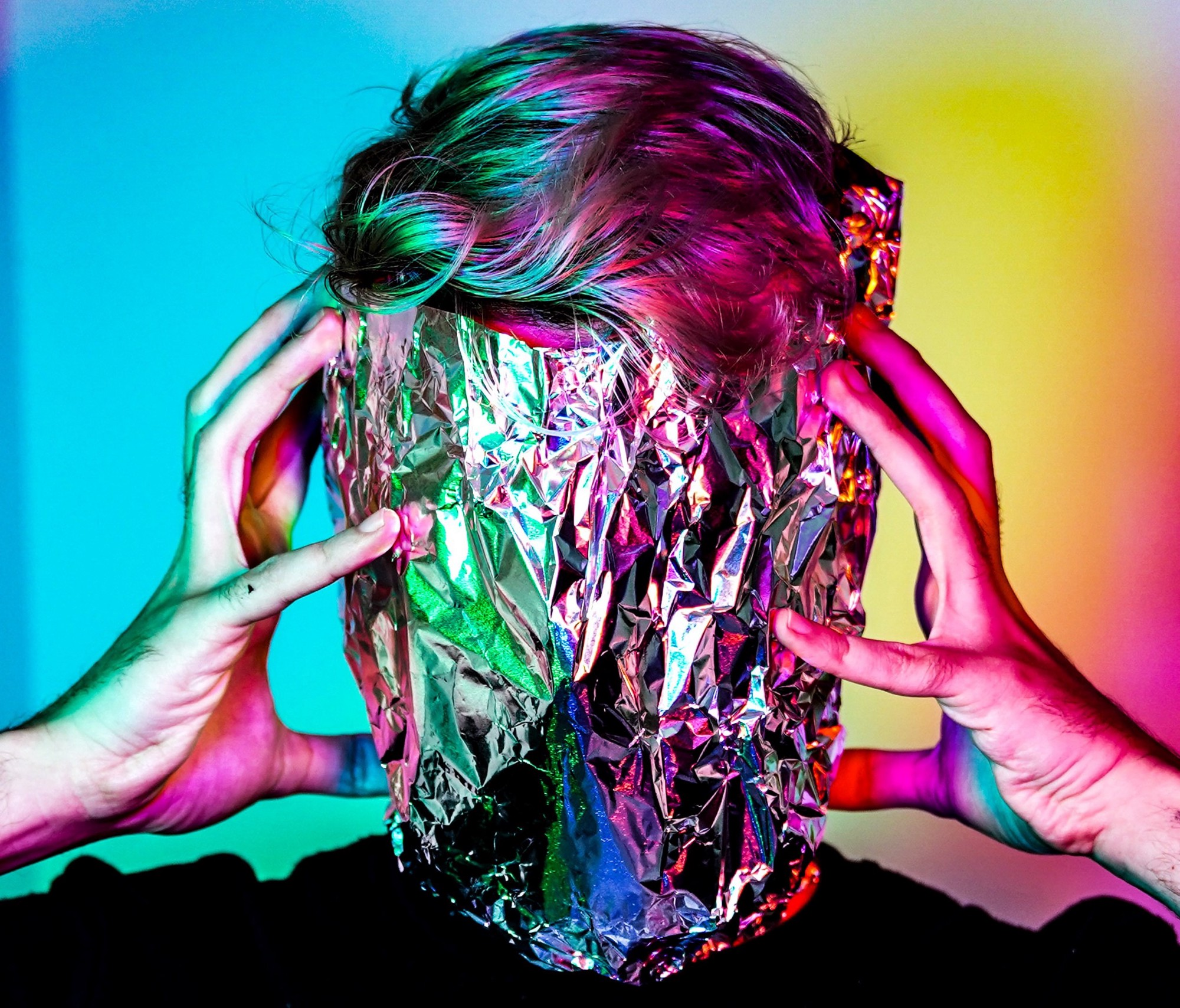 A photo of a person's head with their hands holding a sheet of foil covering their face.