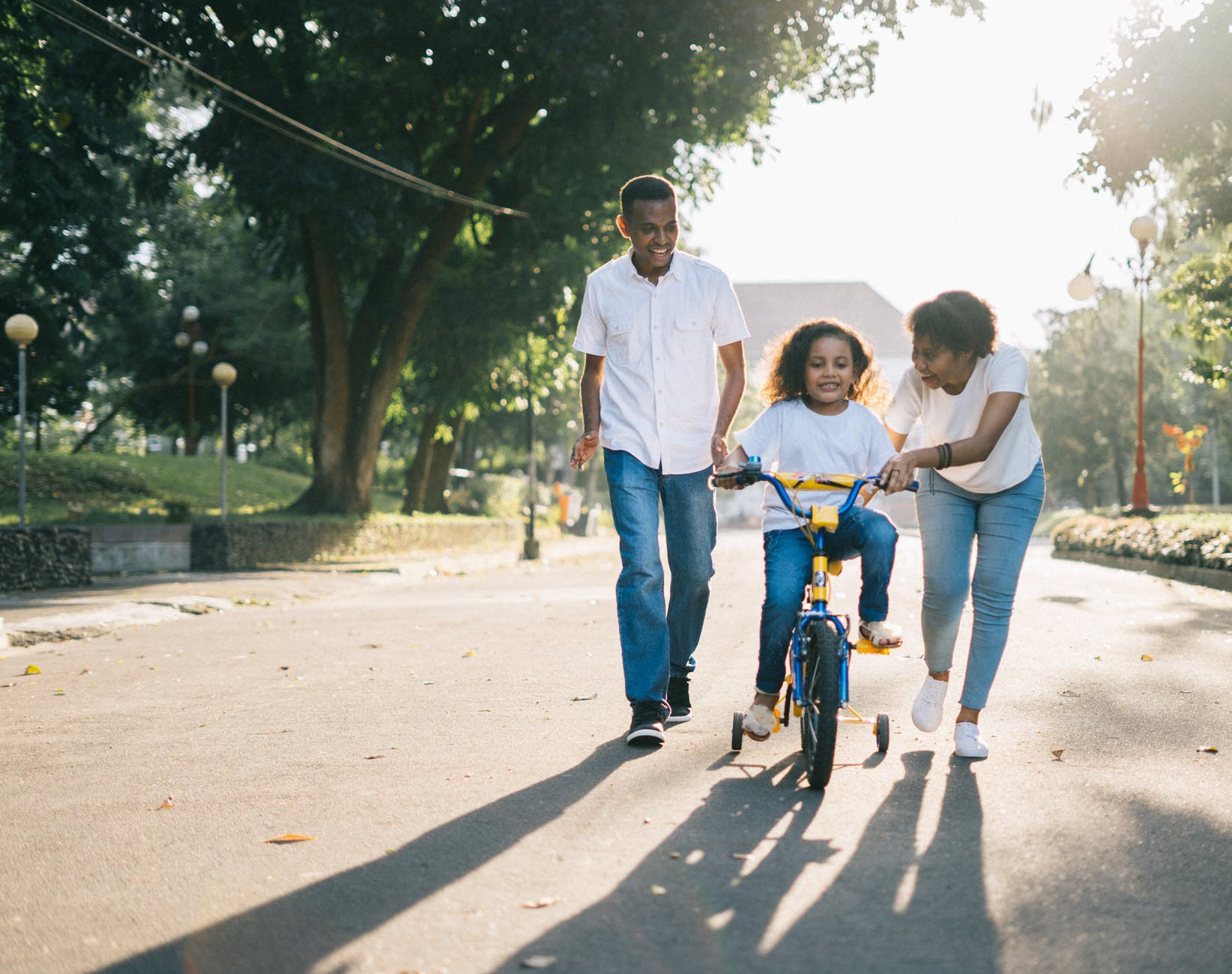 Parents teaching their child how to ride a bike