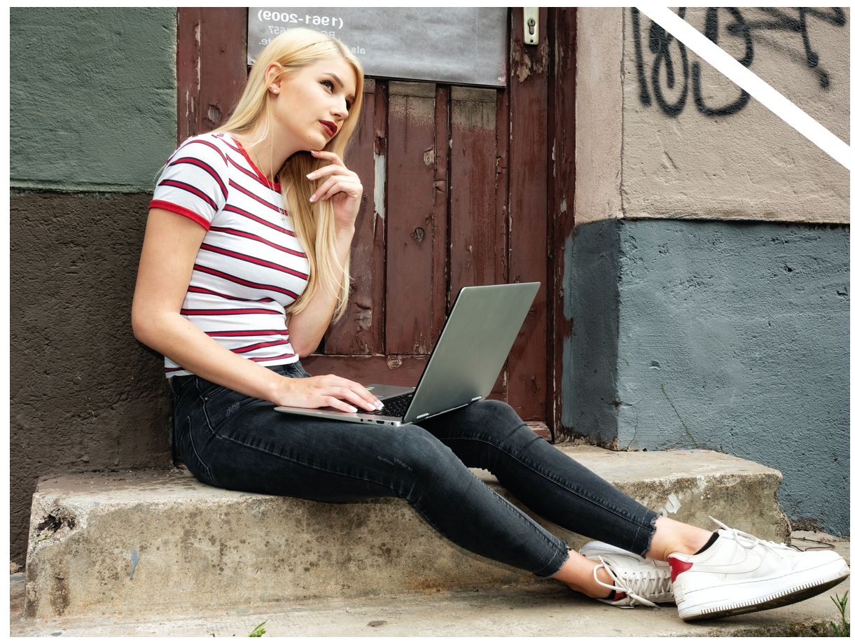 young woman sitting on steps with laptop