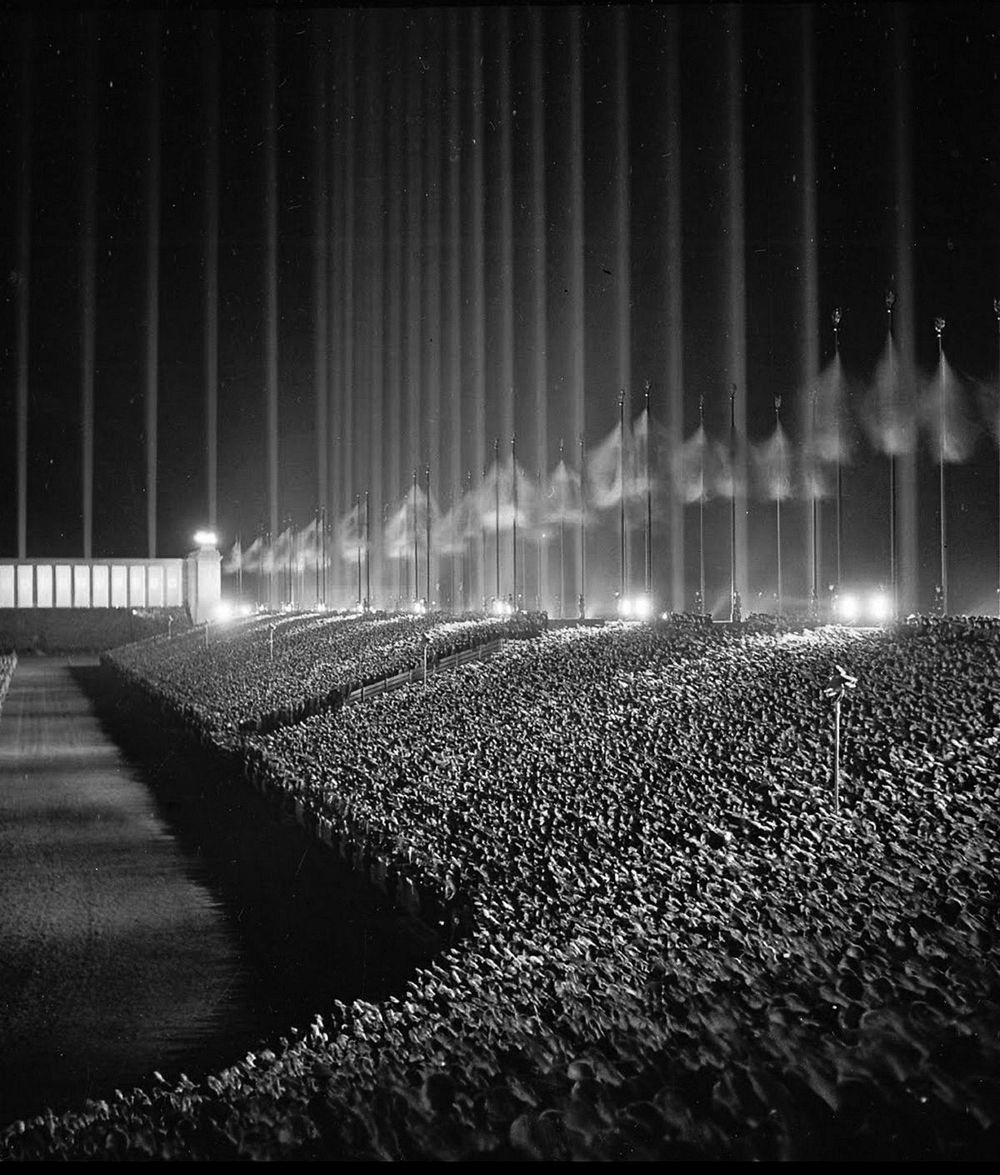 photo of Nuremburg rally with vertical columns of light and massive crowds saluting Hitler