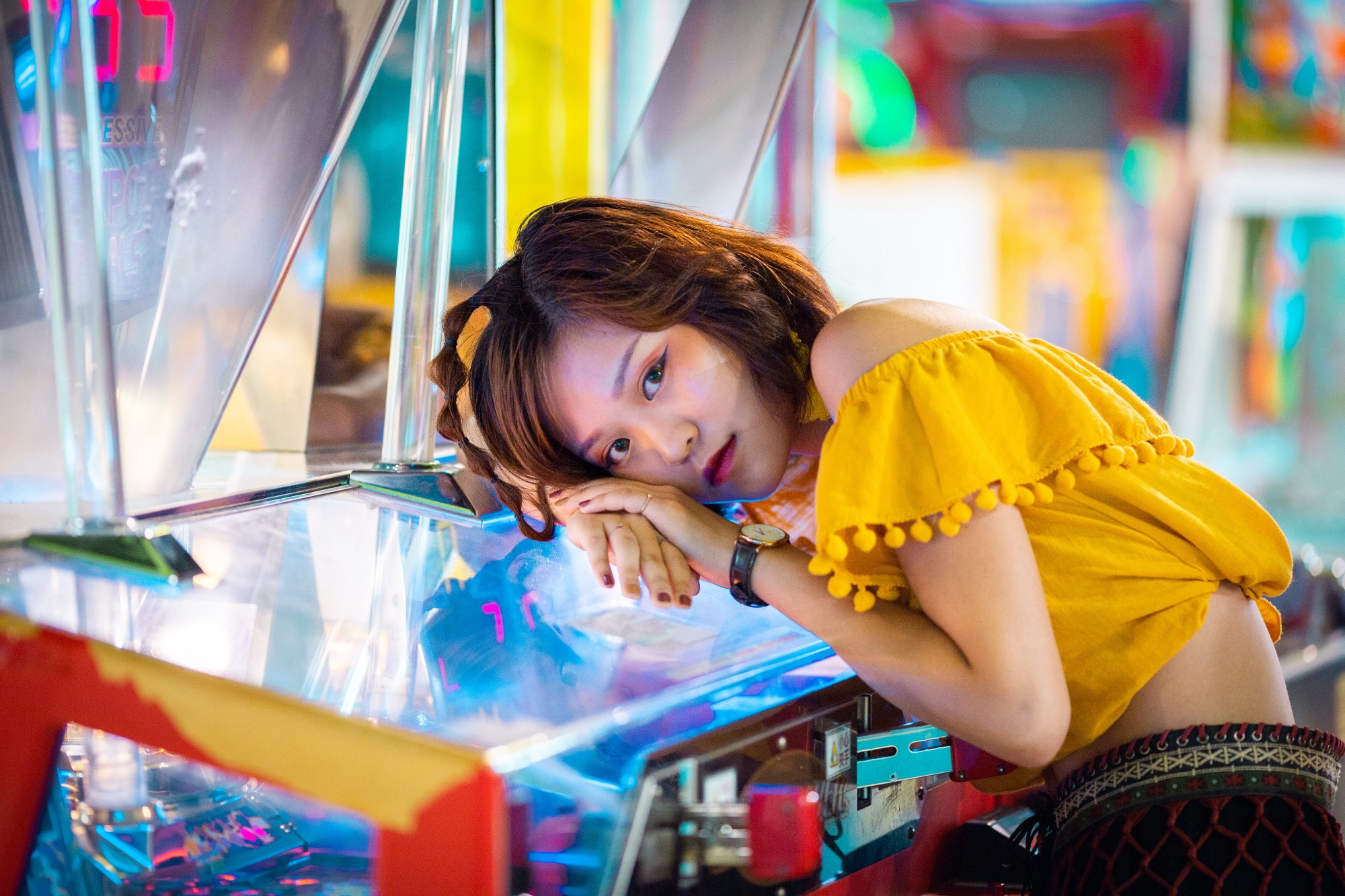 Person—probably a young woman—rests their head on an arcade game while wearing eyeliner and a yellow crop-top blouse.