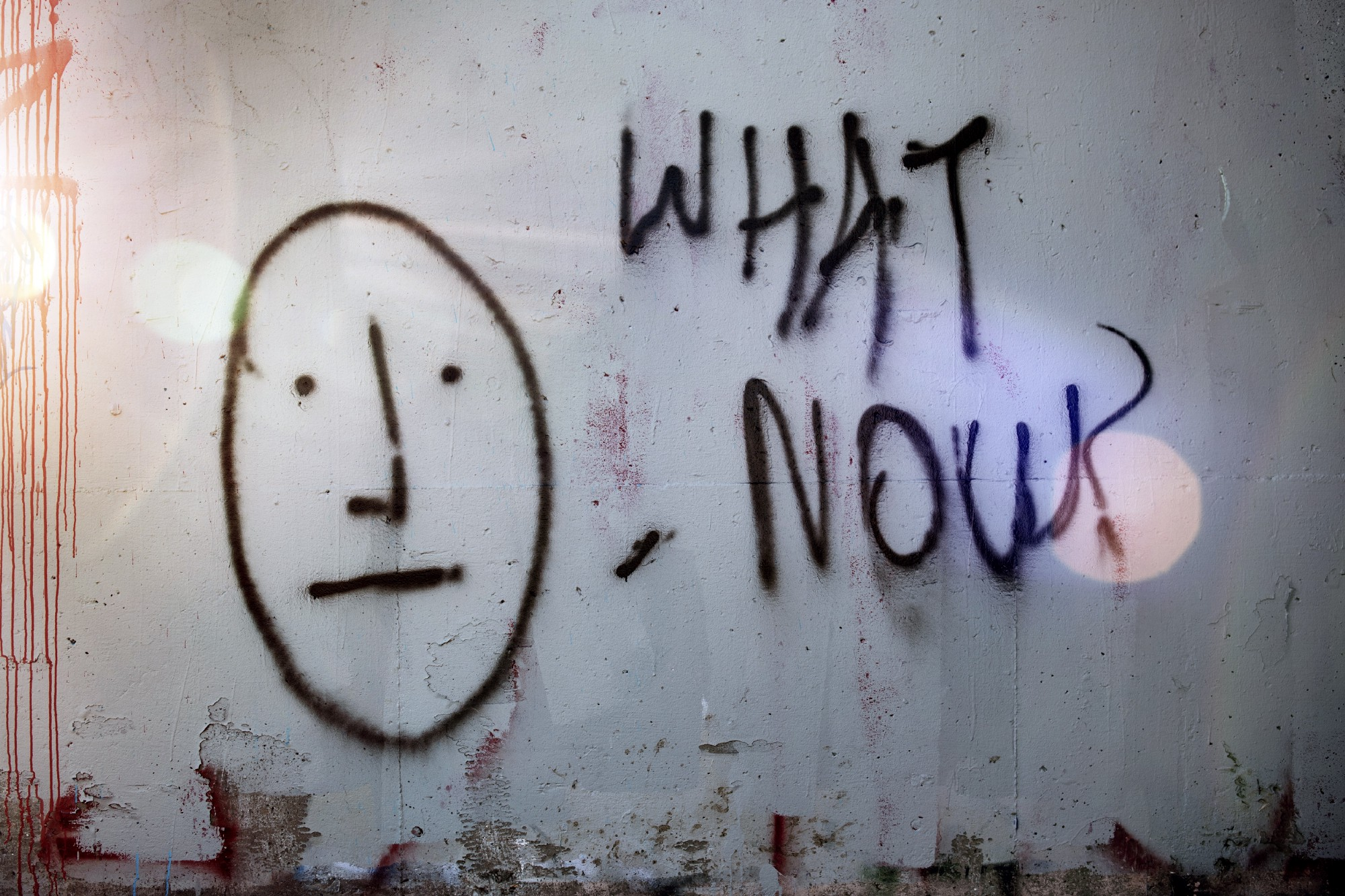 """the words """"what now"""" written on a concrete wall"""