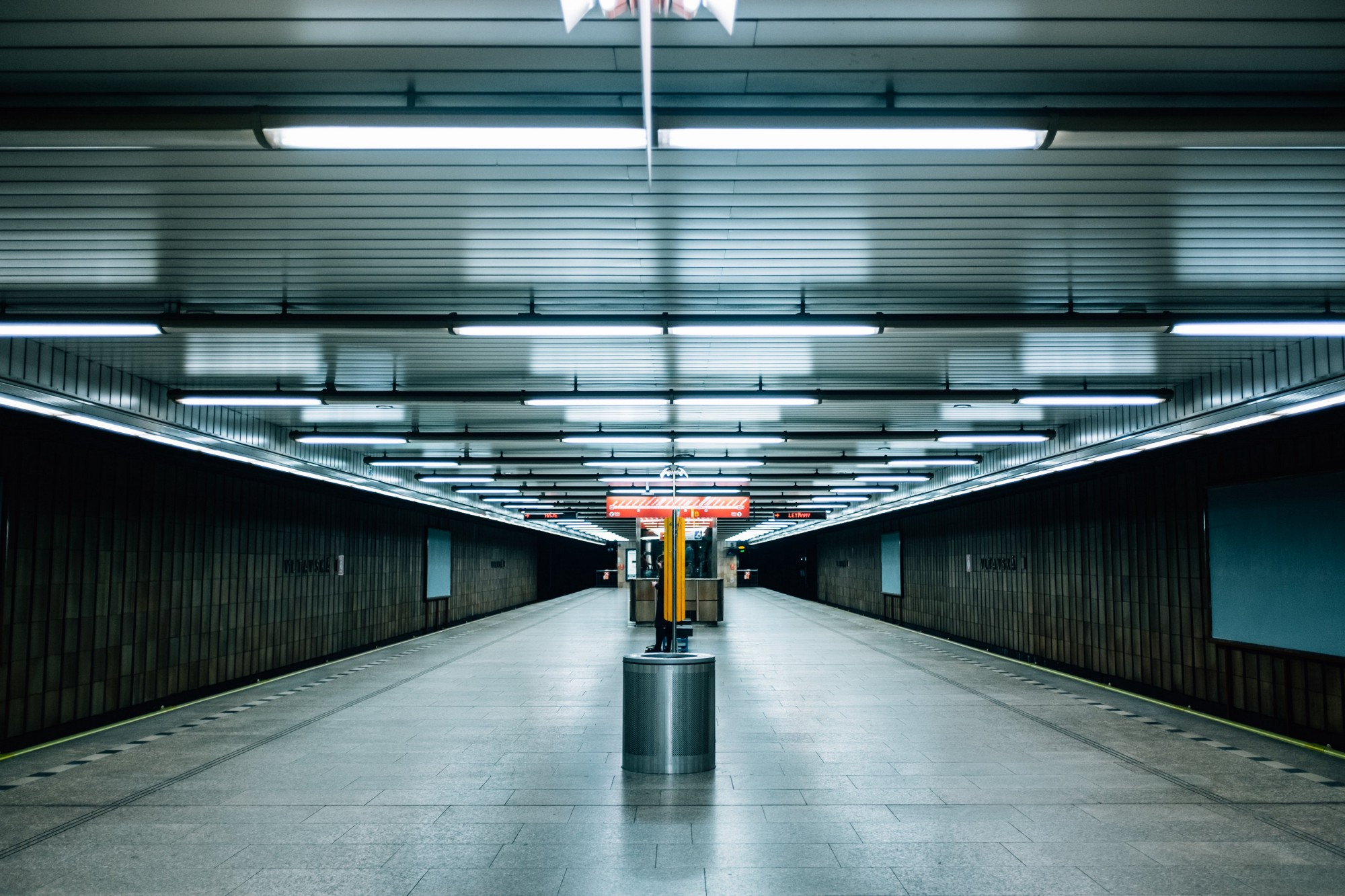 An empty underground station is eerily lit, blues and greys giving a somber mood.