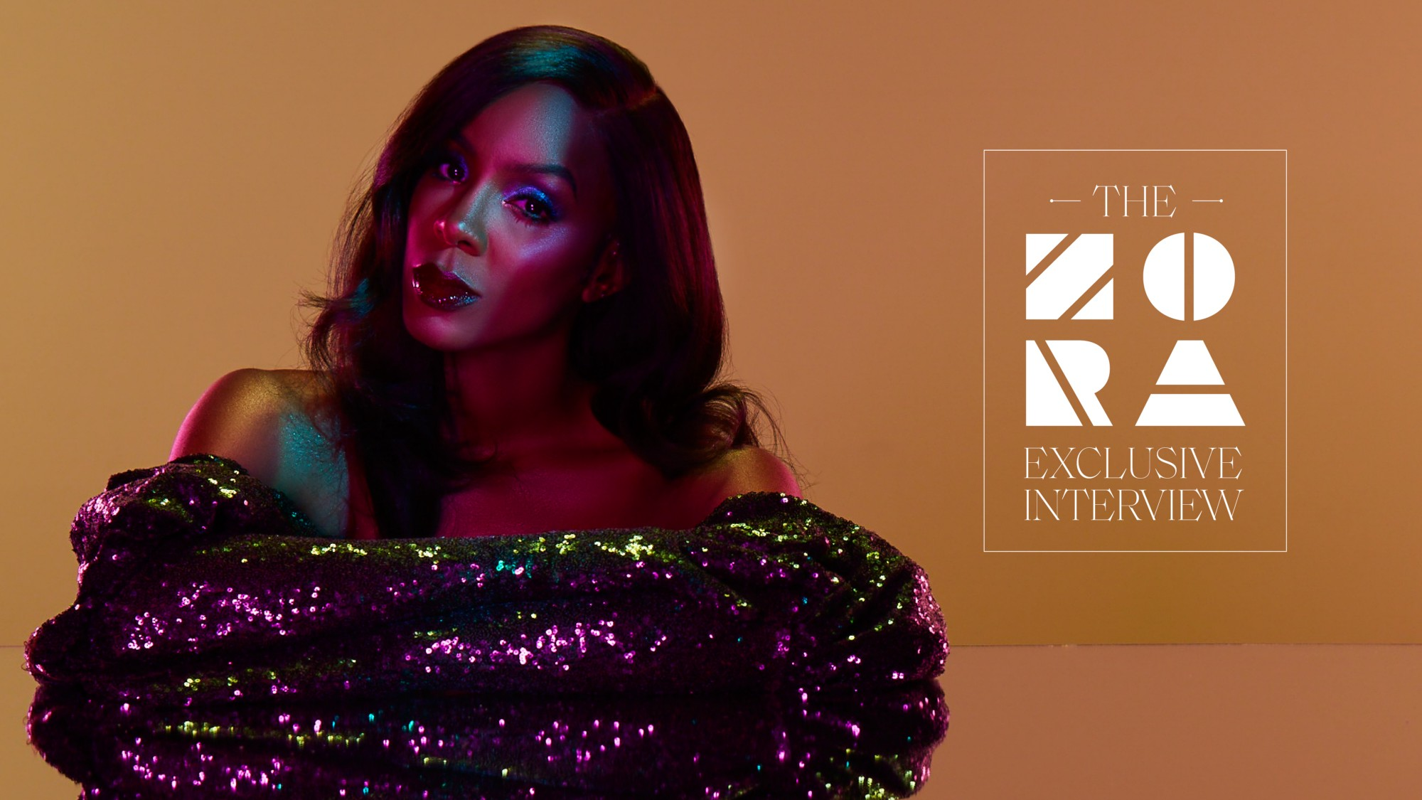 "Photo of Kelly Rowland with a logo that says ""THE ZORA EXCLUSIVE INTERVIEW"" on the right."