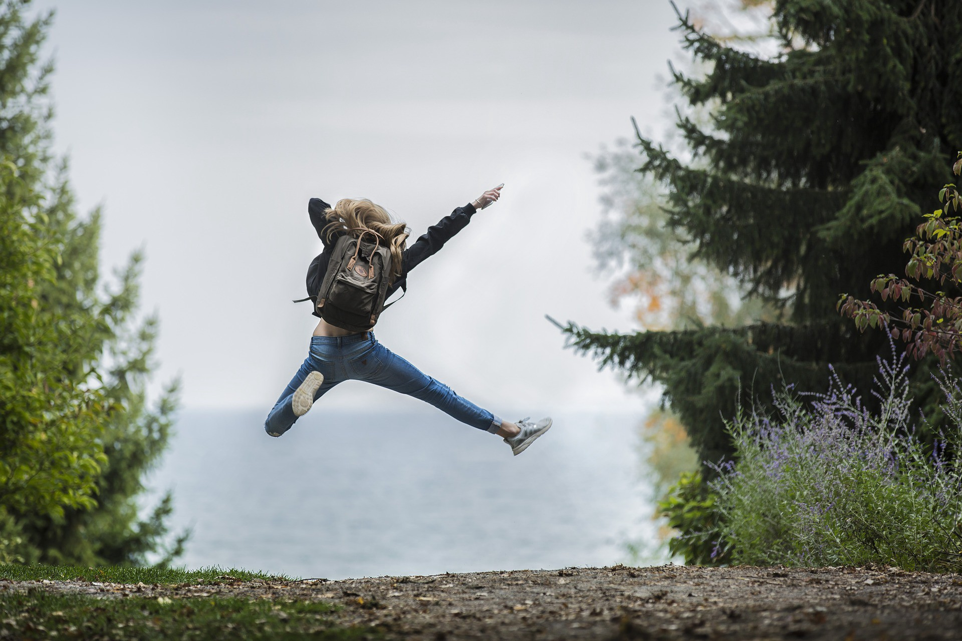 A young girl leaping with joy with her arms wide up in the air