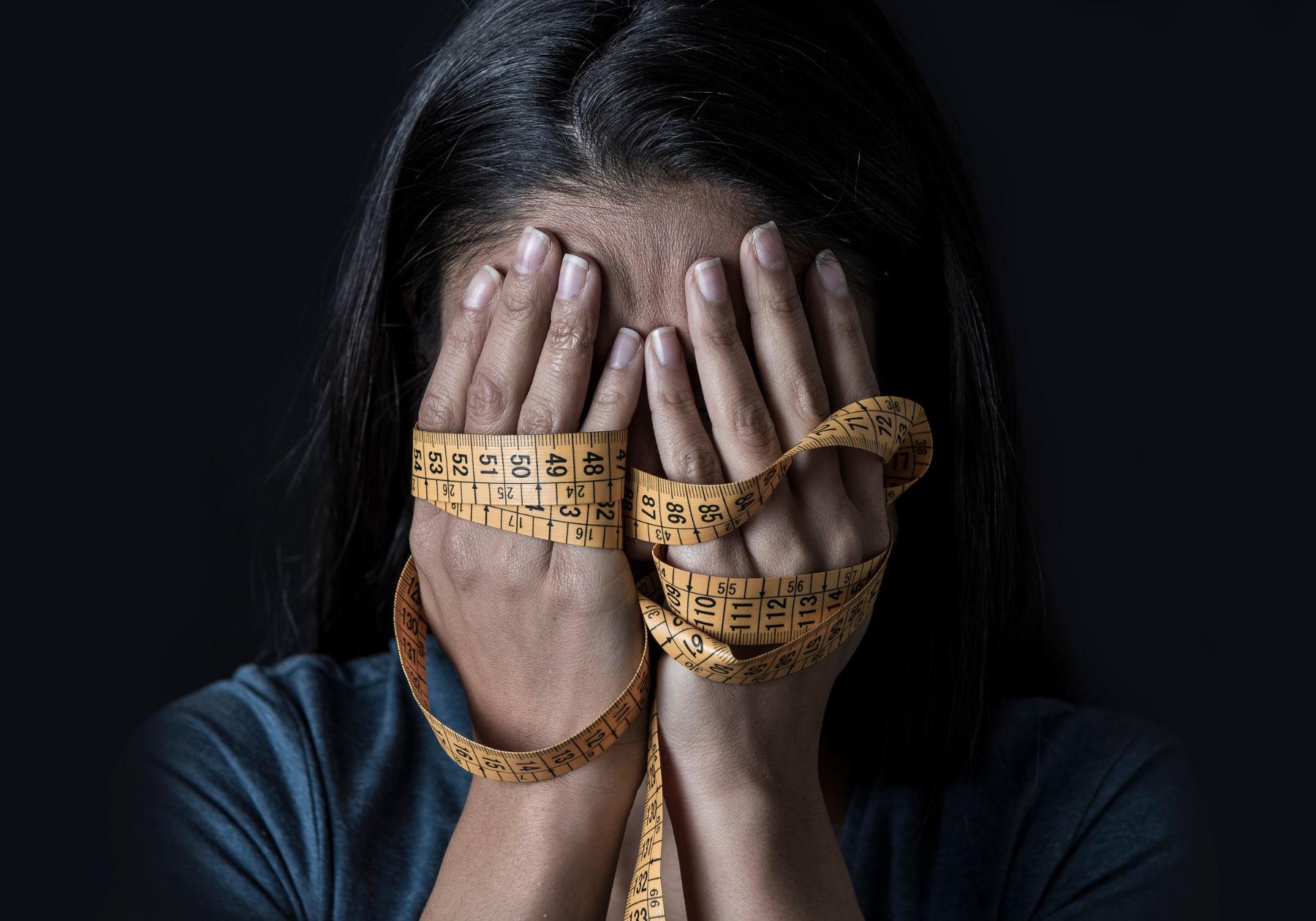 A brown-skinned woman with straight black hair covers her face with her hands. A yellow tape-measure is wrapped around her hands.