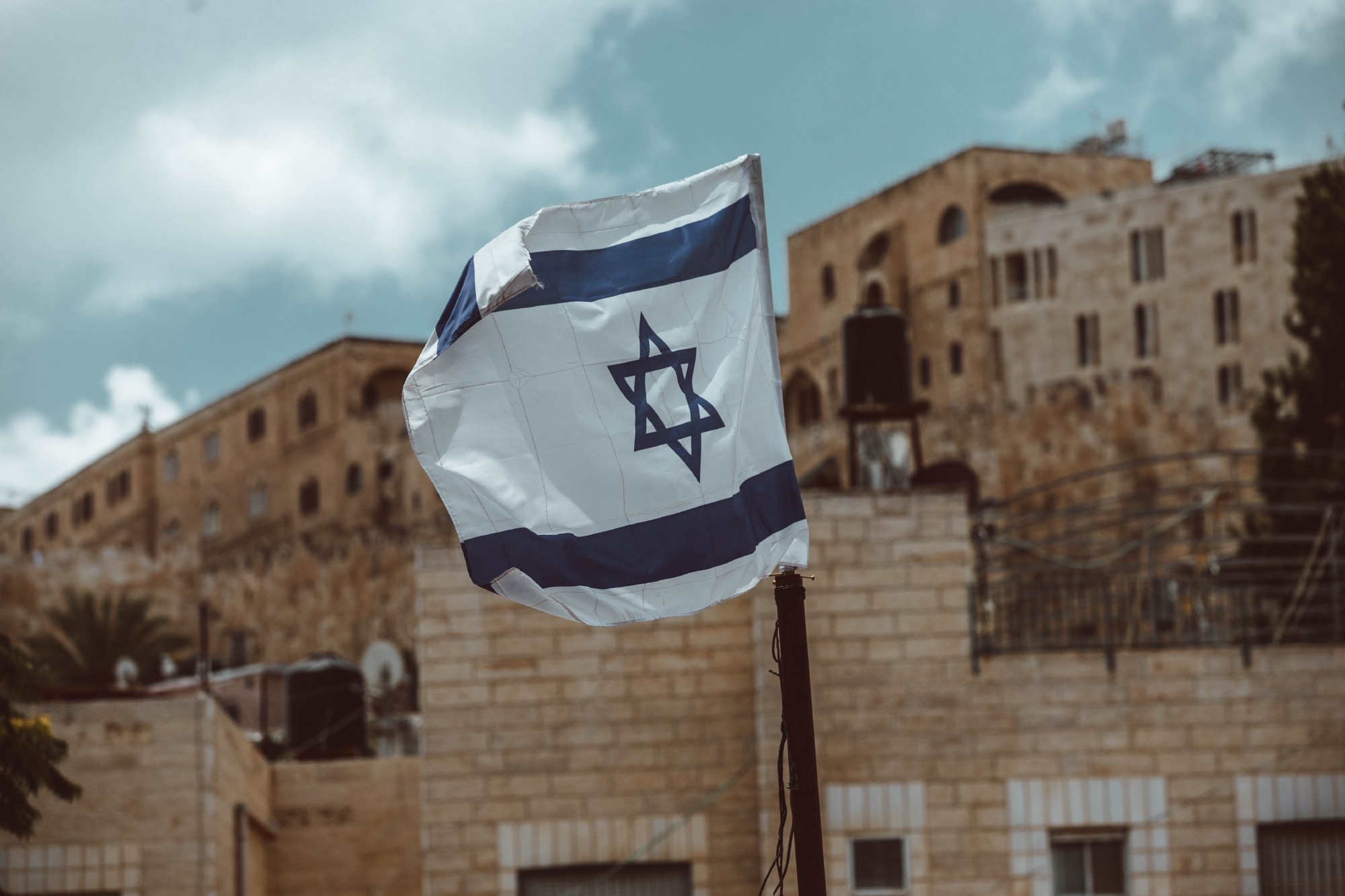 The flag of Israel was adopted on 28 October 1948, five months after the establishment of the State of Israel. It depicts a blue hexagram on a white background, between two horizontal blue stripes. That symbol in the center represents the Star of David, a Jewish symbol dating from late medieval Prague, which was adopted by the First Zionist Congress in 1897.