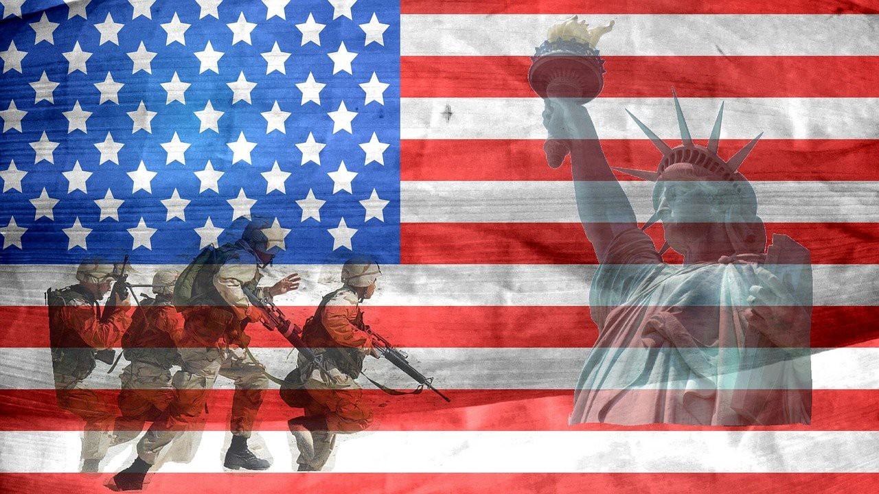 An American flag with a photo of the Statue of Liberty and four military members.
