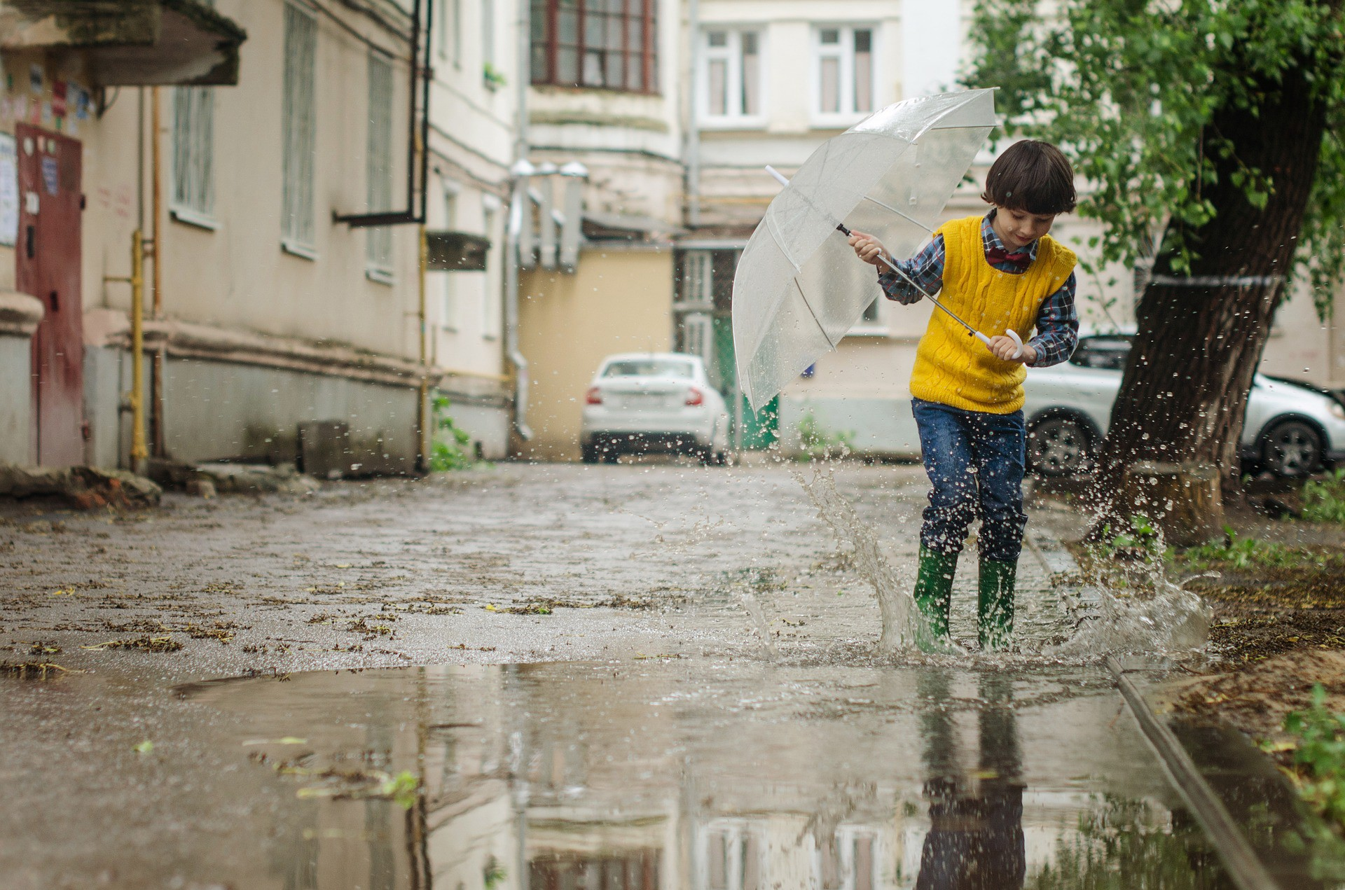 A happy boy with umbrella jumping in a puddle of water in a street