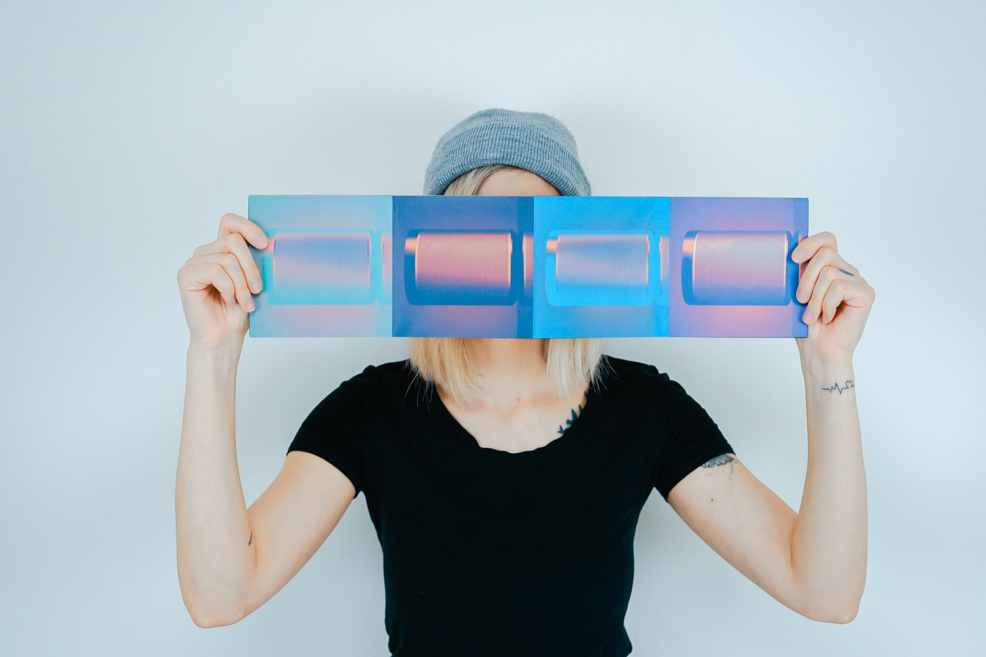 A woman holds art in front of her face. The art is four squares of varying blue shades.