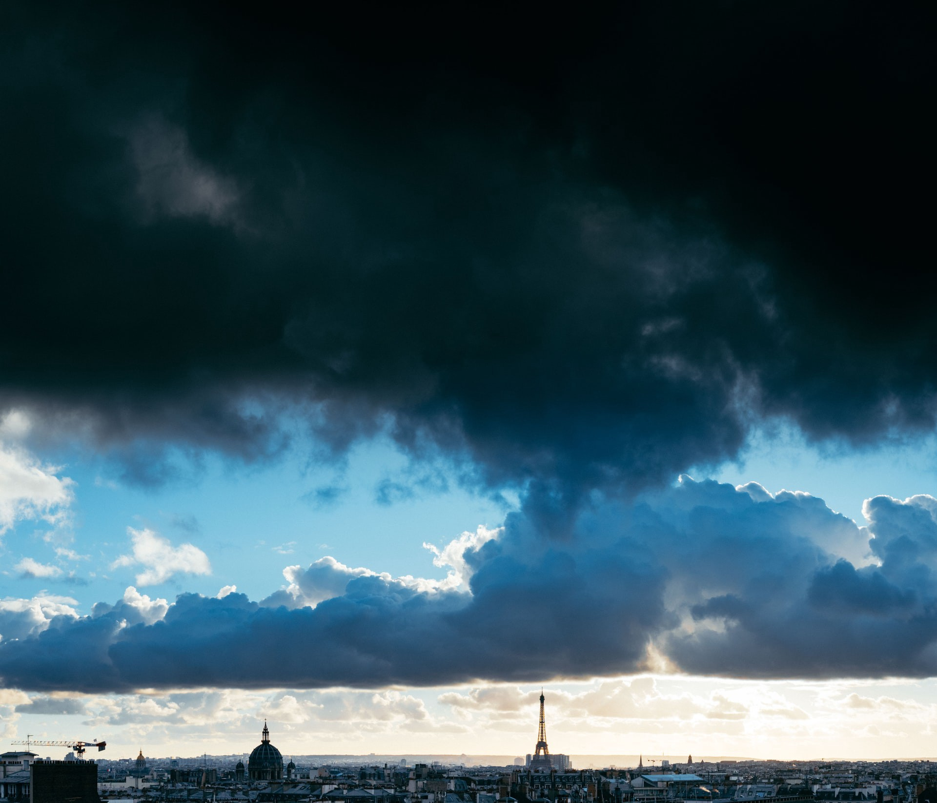 Silhouette of the Eiffel Tower in Paris against a backdrop of dark clouds.