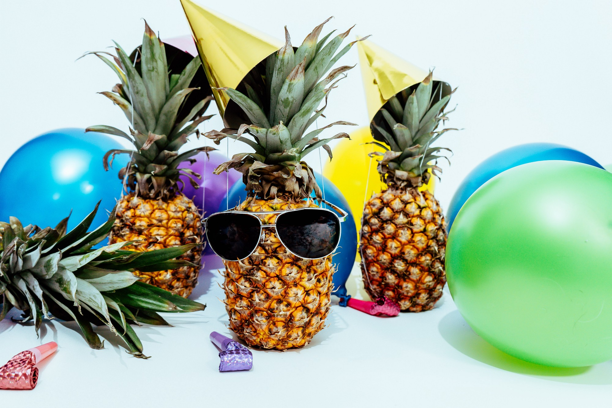 Three pineapples with party hats on and surrounded by birthday balloons