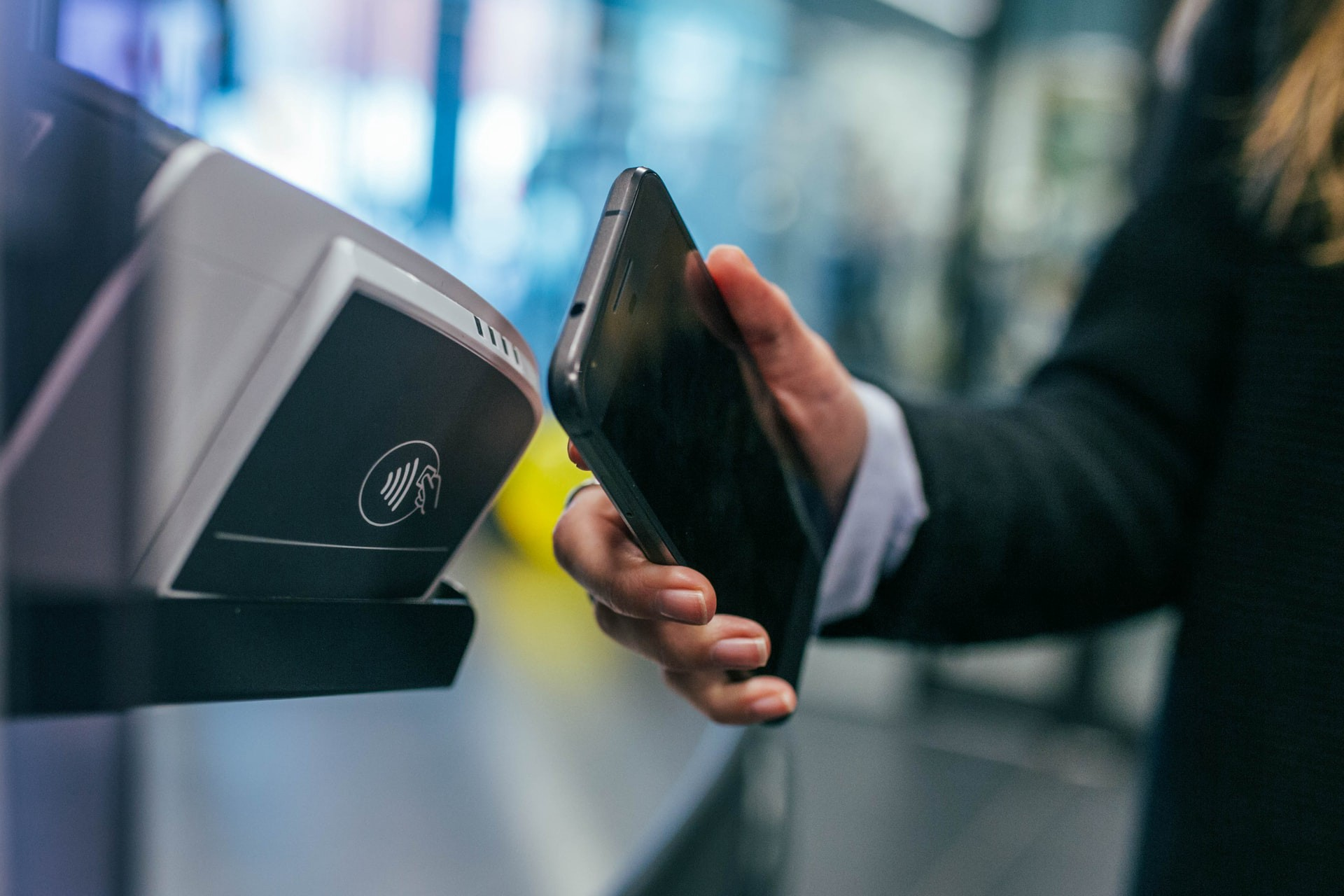 Colour photograph of a woman holding her smartphone up to a payment terminal.