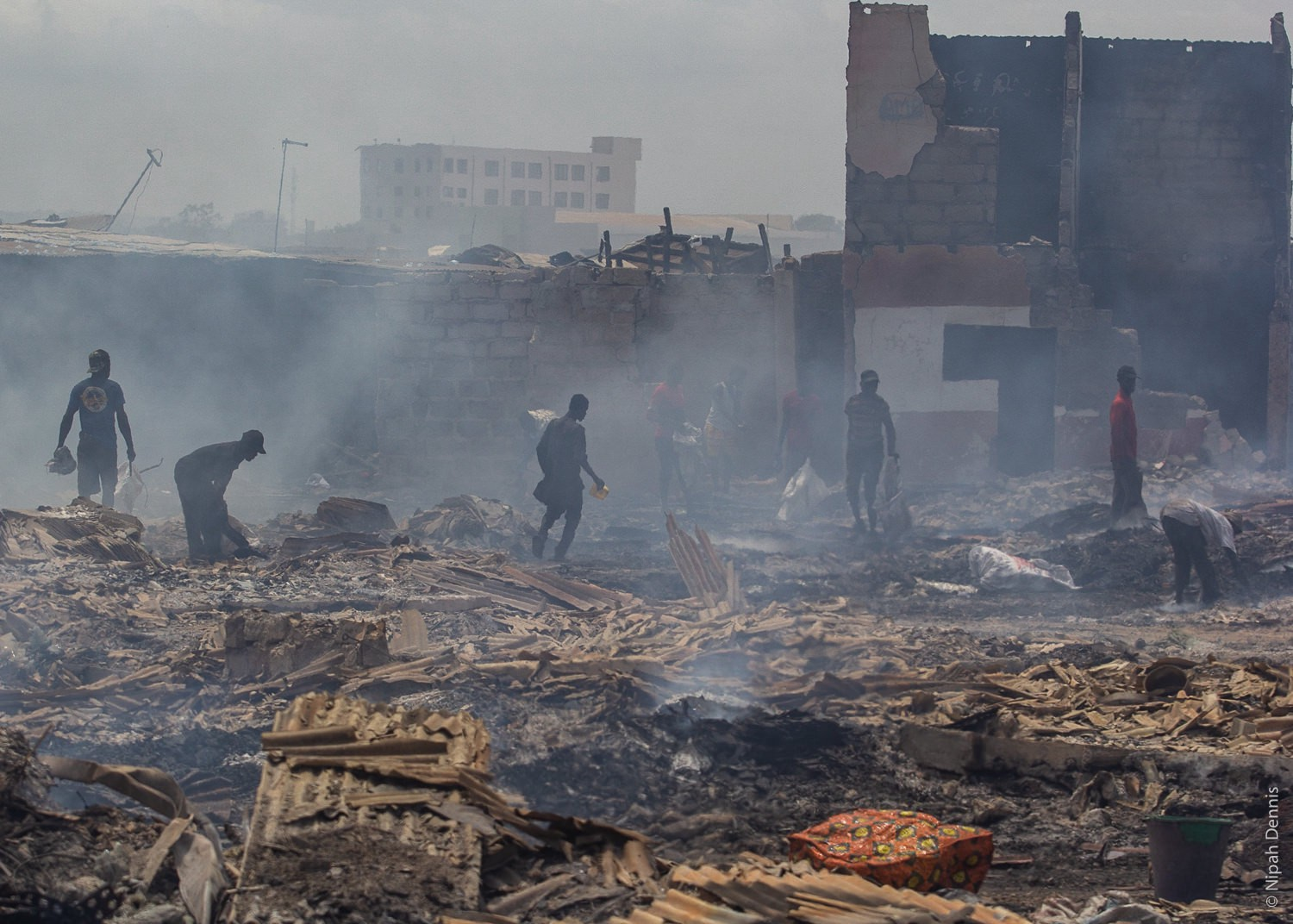 Residents try to find valuables in the debris after homes burn to the ground in Agbogbloshie, Accra, Ghana. April 7, 2020. Ph