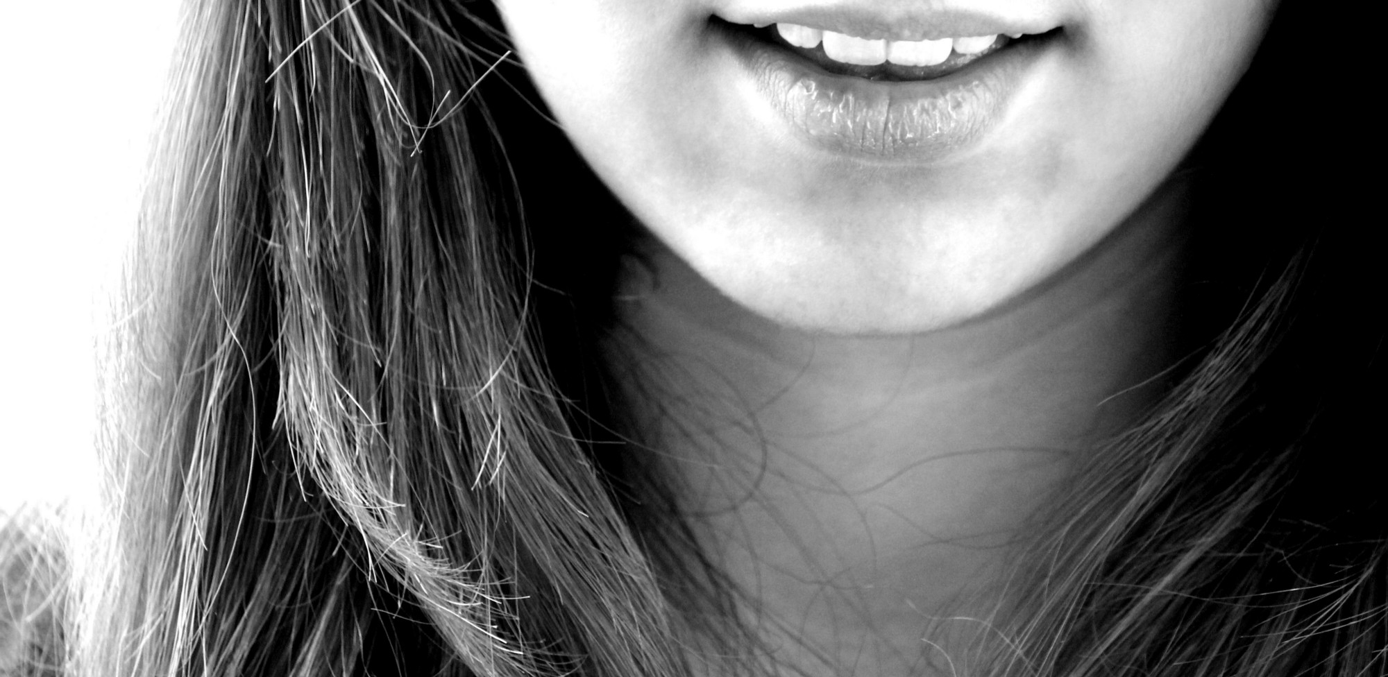 Black-and-white photo of the lower half of a woman's face only showing her mouth, which is smiling