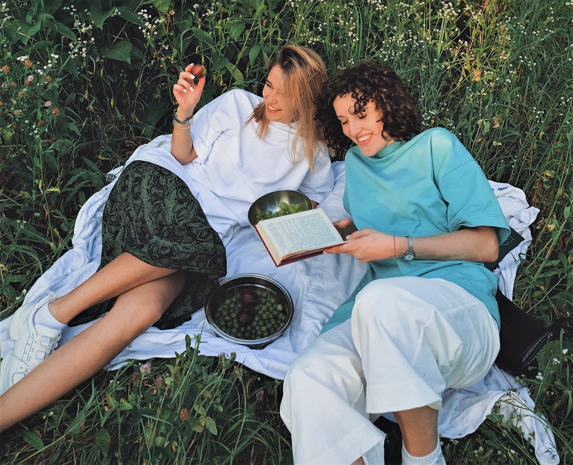 two smiling girls sitting on white blanket on green grass reading book