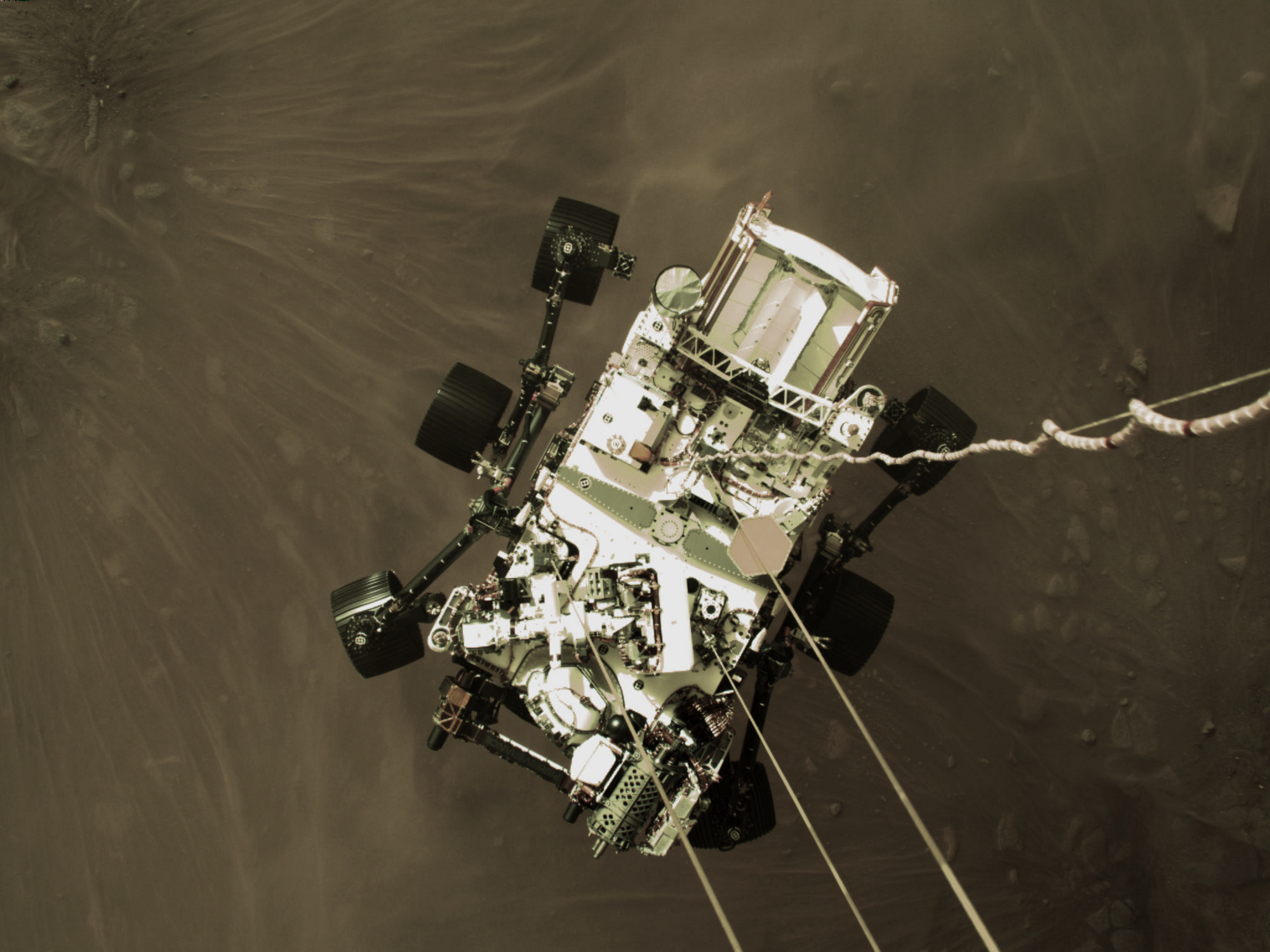 A photo taken by Perseverance's landing jetpack as it lowers the rover onto the Martian surface.