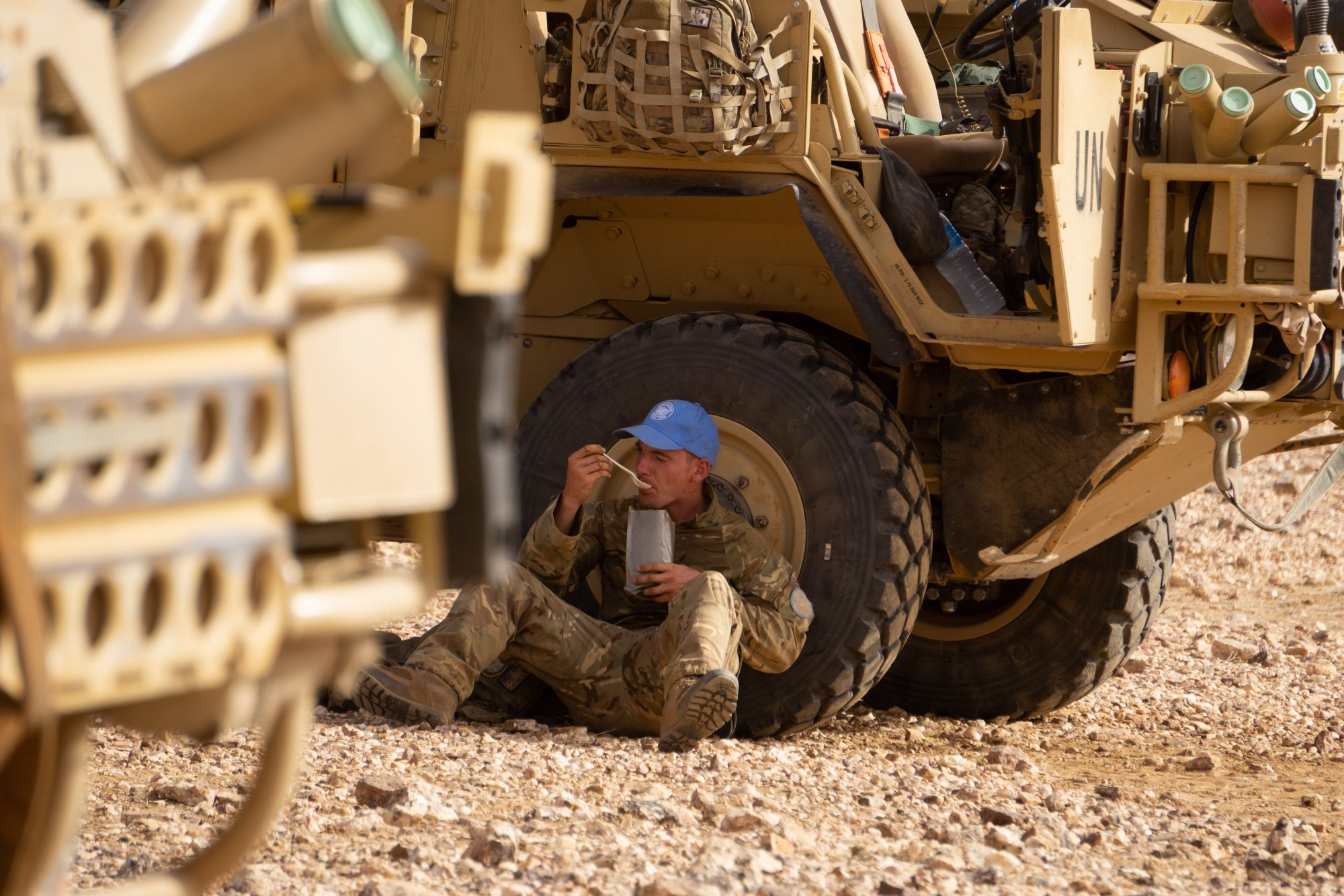 A British peacekeeper stops to eat his ration.