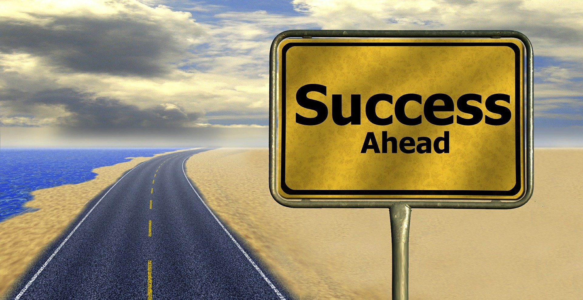 Yellow road sign saying success ahead