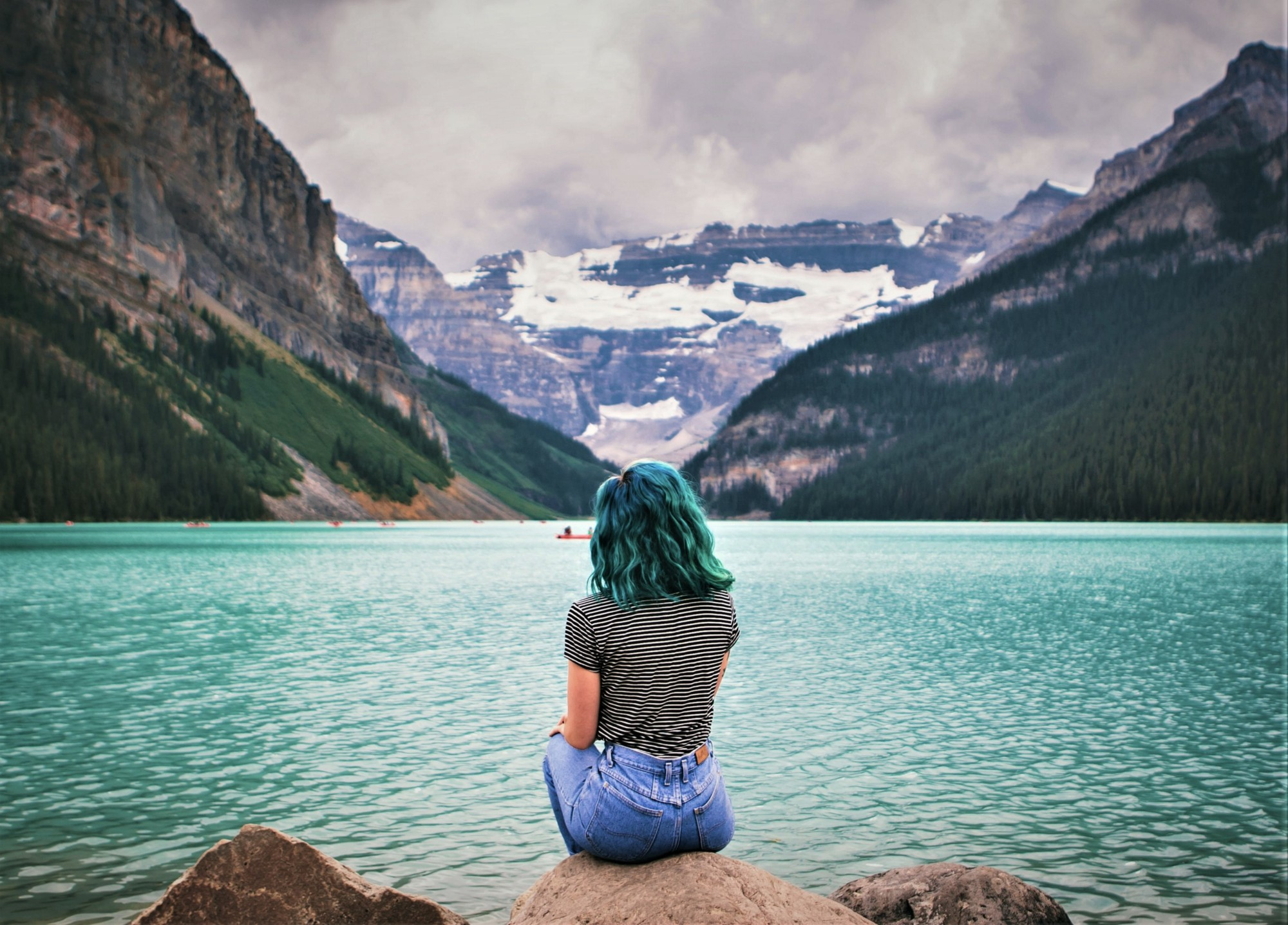 rear view of woman wearing blue jeans sitting on a rock looking out over lake and mountains