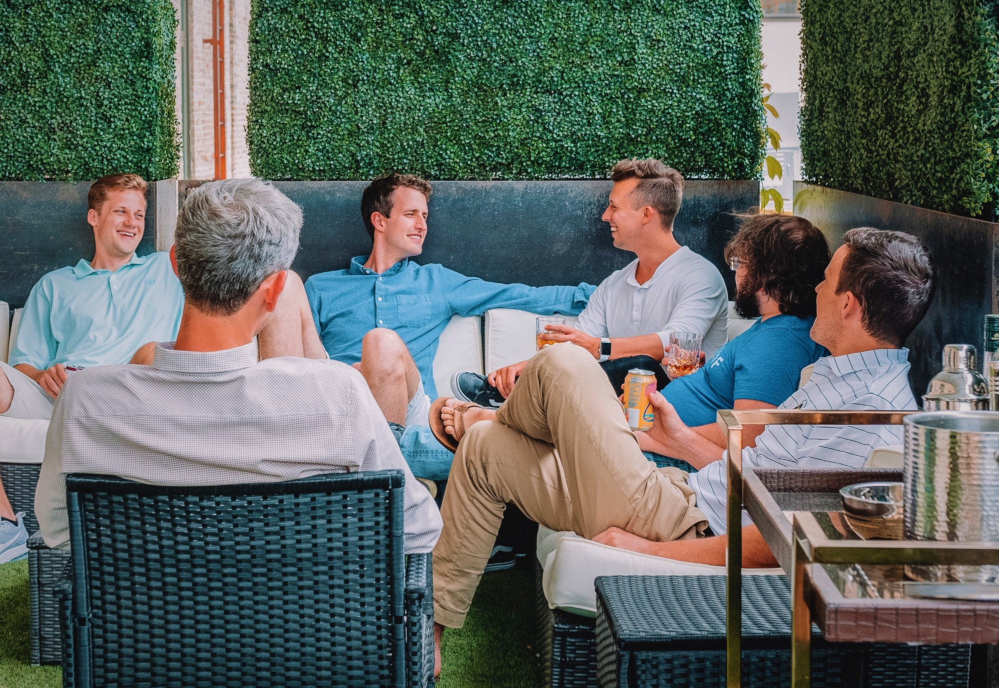 Six men sitting on couch outdoors having a conversation
