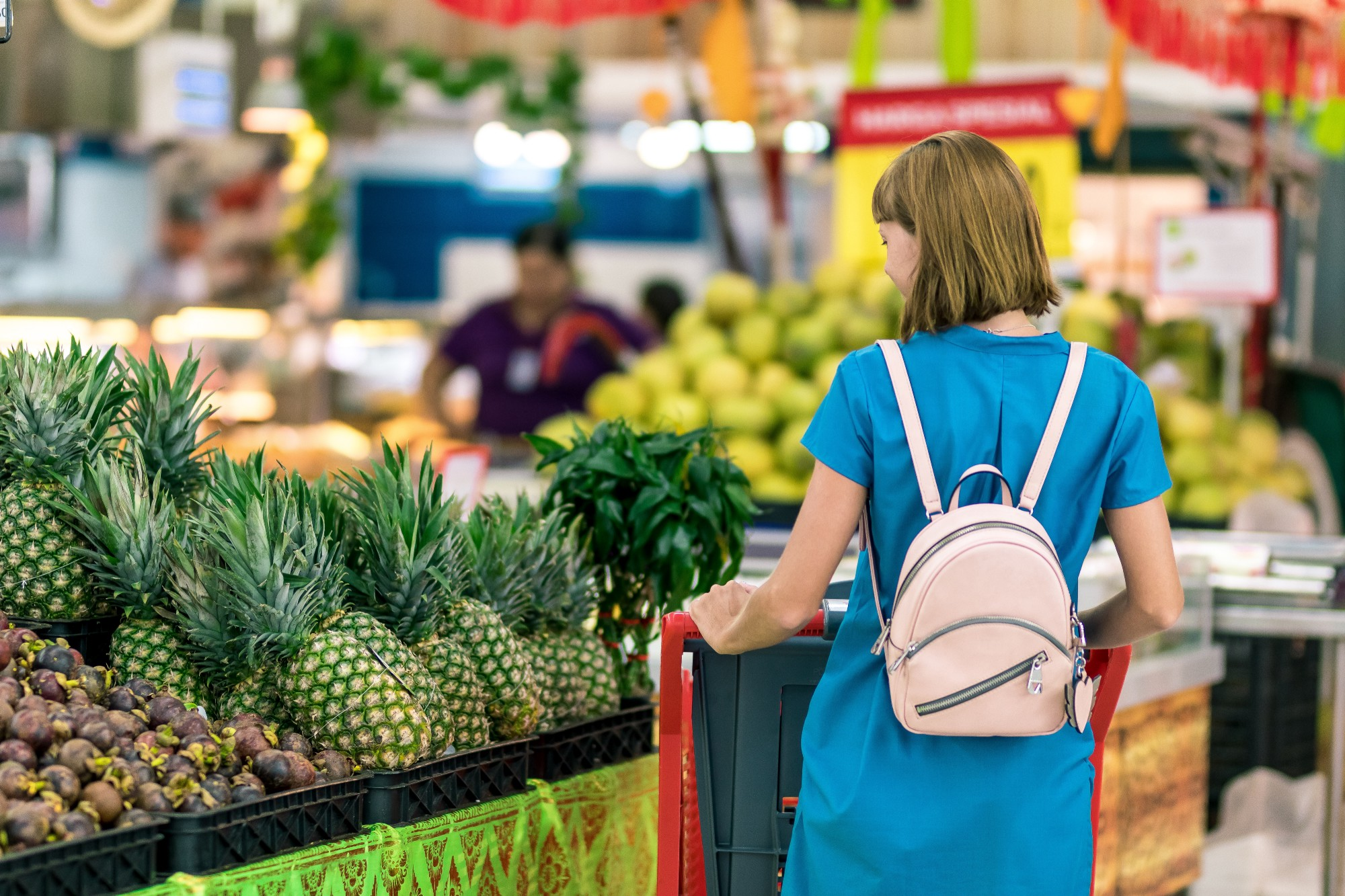 woman in blue dress with white backpack pushing shopping cart in store shopping for pineapple fruit vegetables