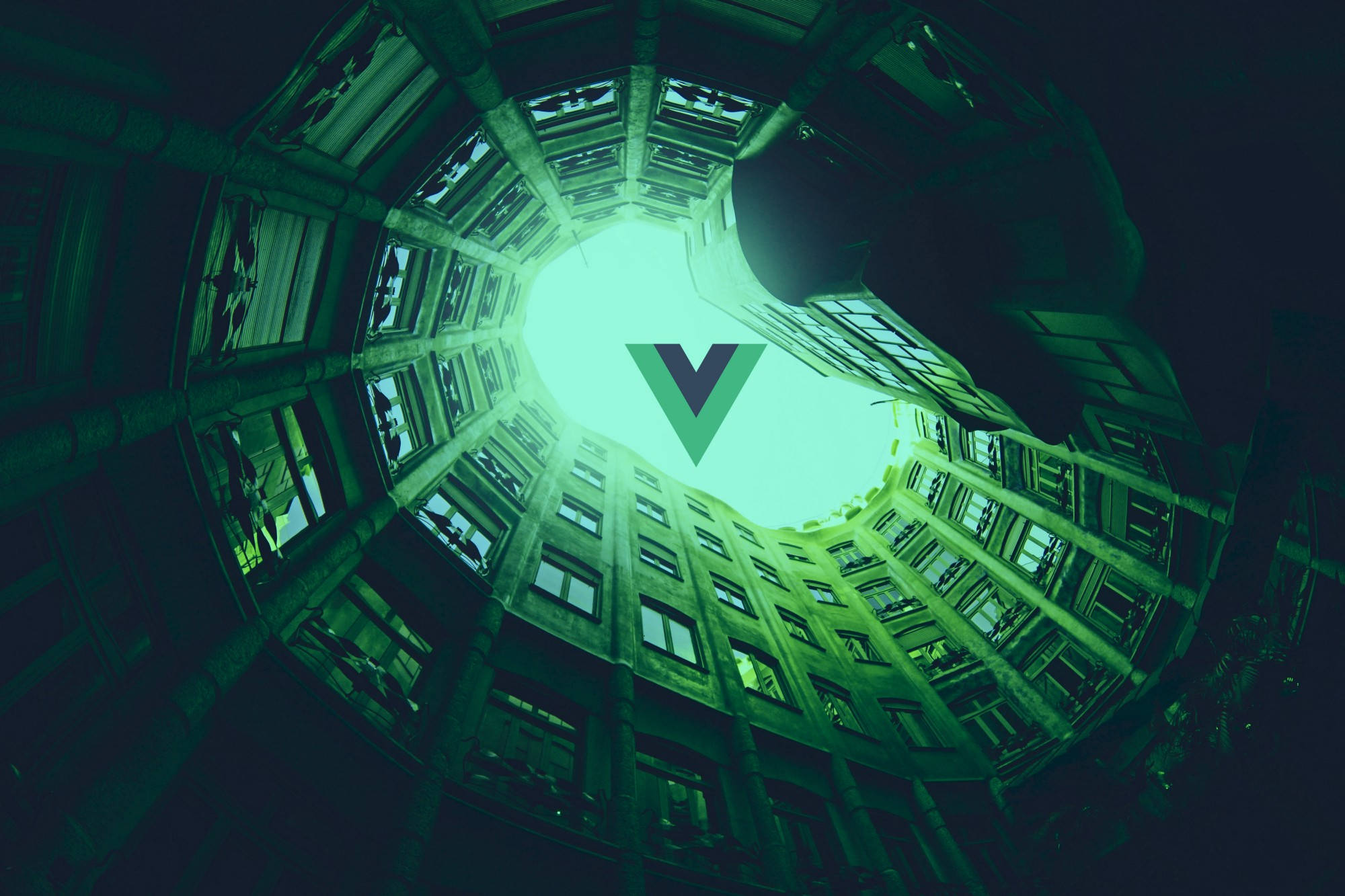 The view from an inner courtyard, enclosed by buildings, themed in Vue's brand colors. In the sky, there thrones the Vue logo