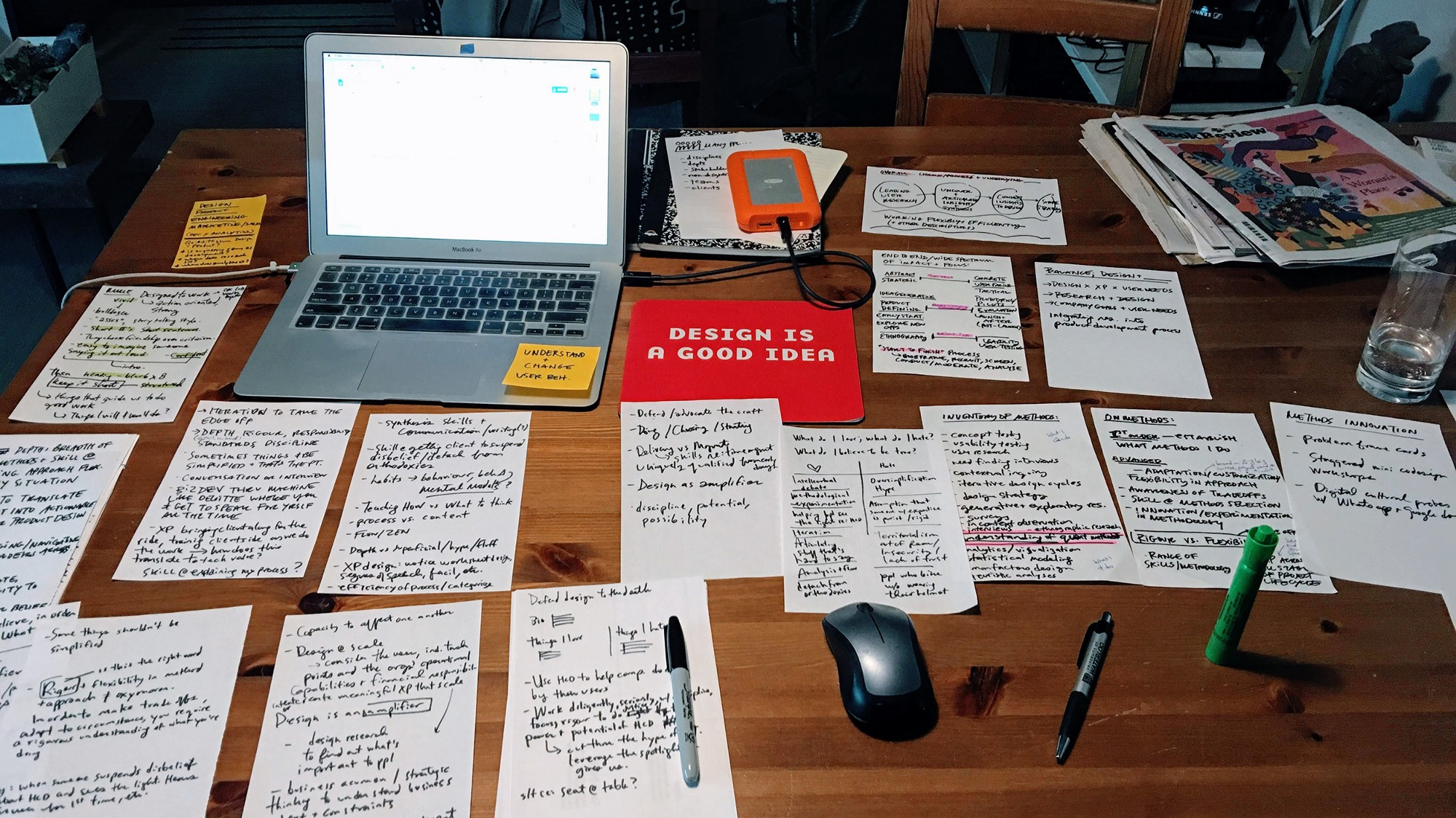 An open laptop sits on a wooden table covered with half sheets of handwritten notes