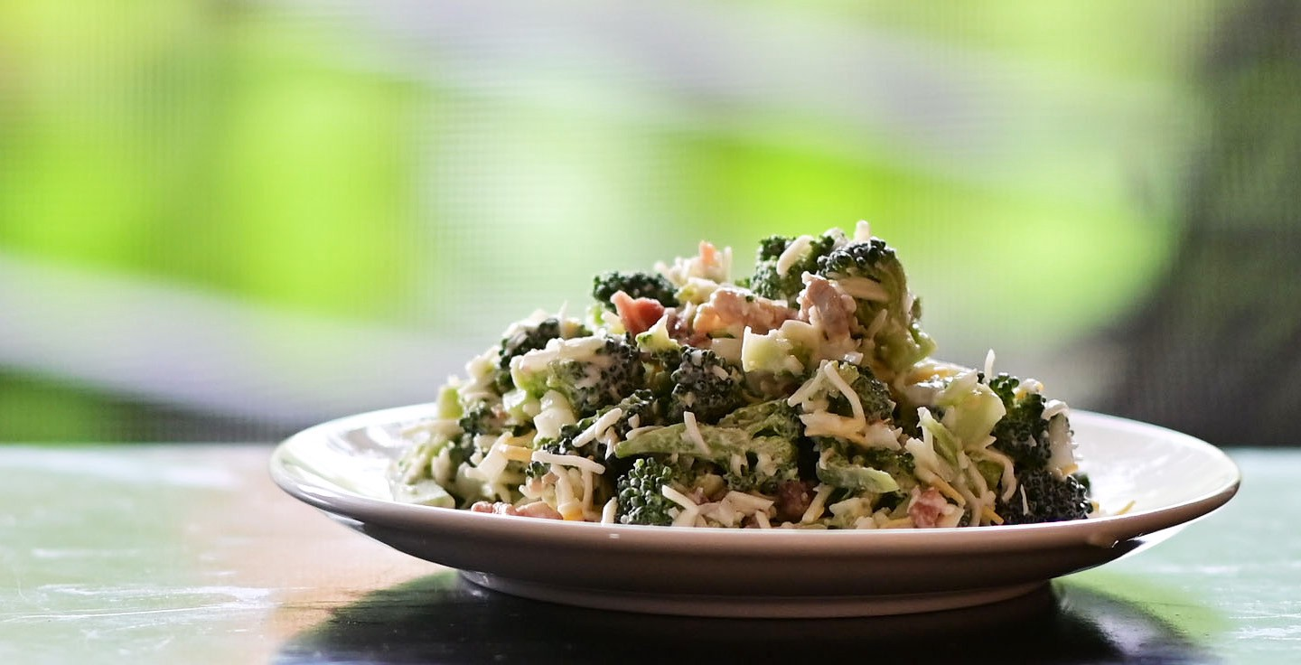A serving of broccoli bacon salad on a white plate, with an obscured green hued background.