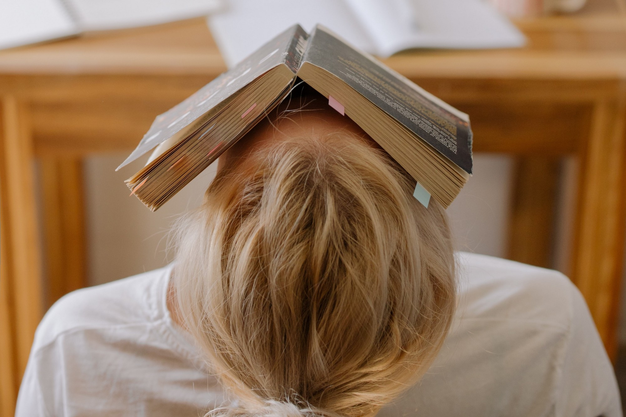 girl with her head tipped back and a book covering her face