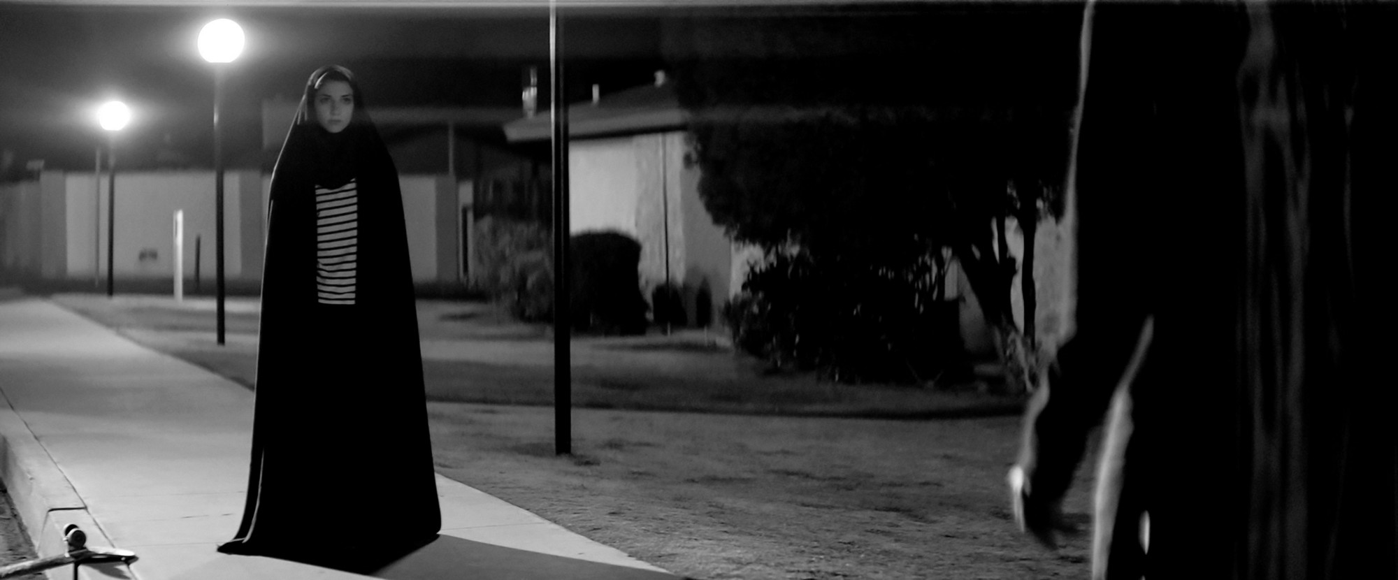 A female vampire wearing a chador stands looking at an unseen character.