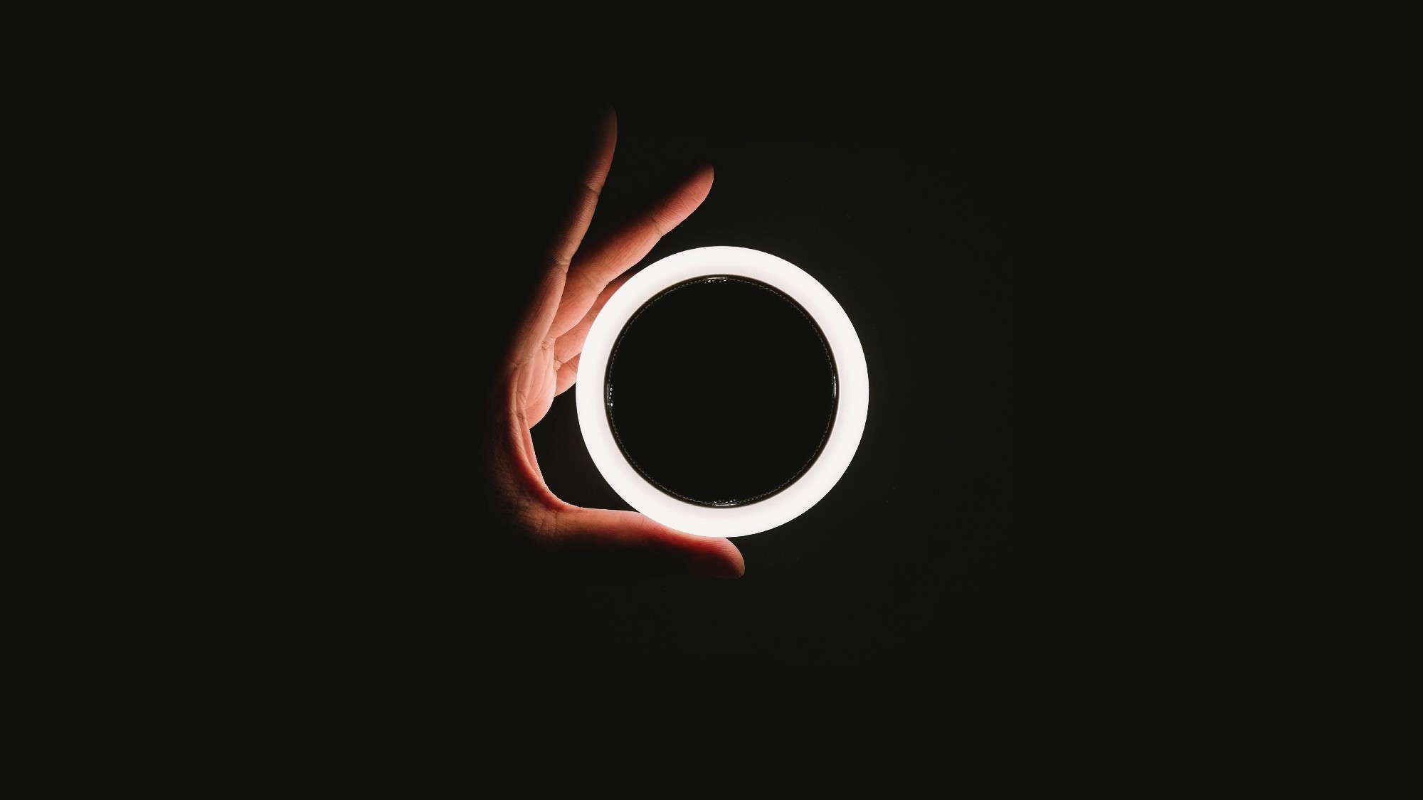 Hand holding large ring of light.