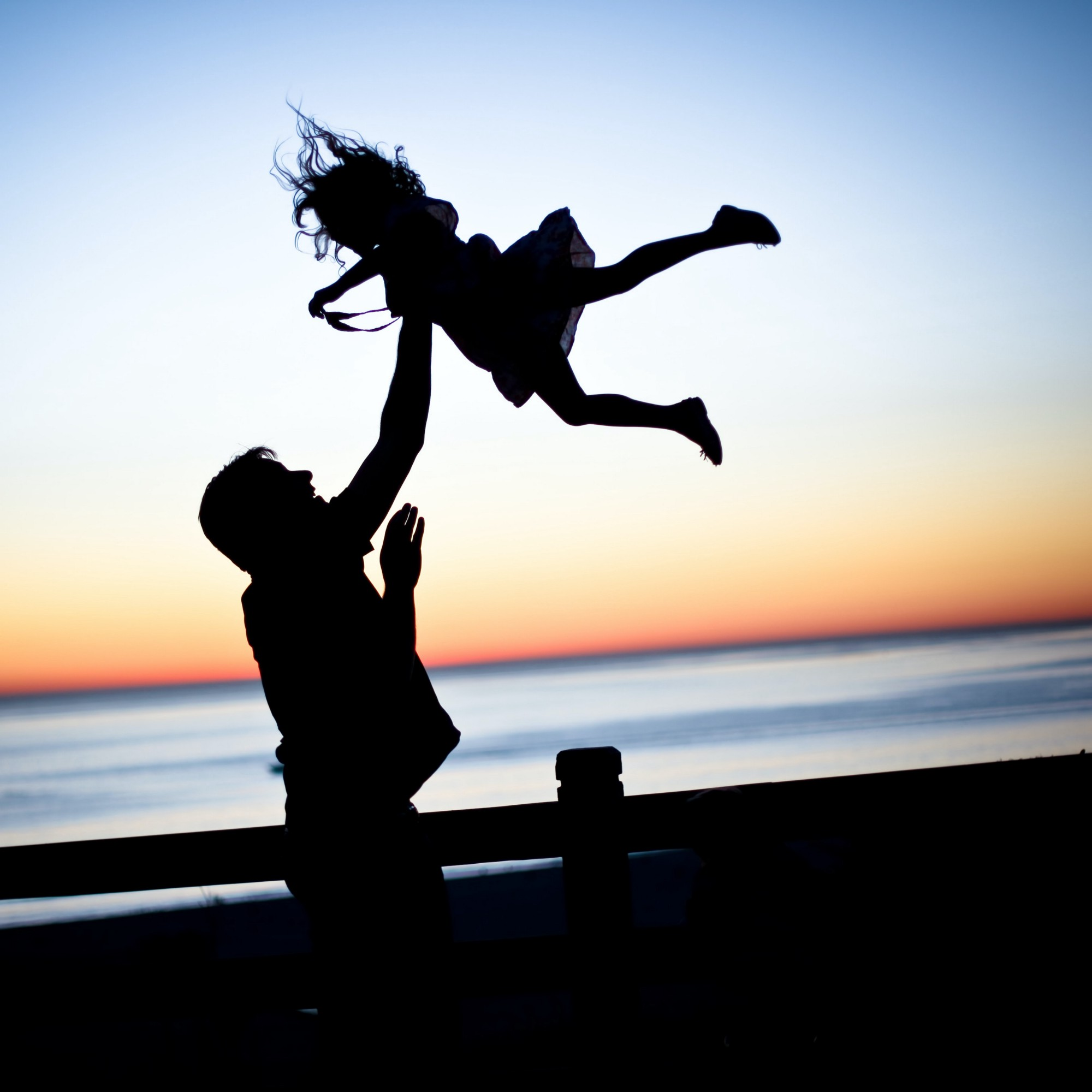 Silhouette of man or father tossing little girl in the air for fun with a sunset backdrop