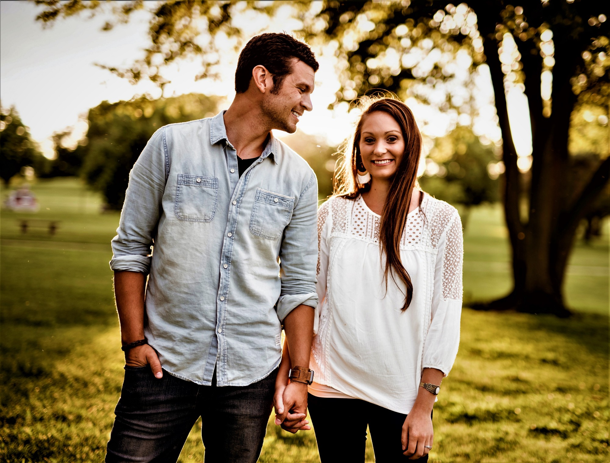 happy young couple standing in park holding hands