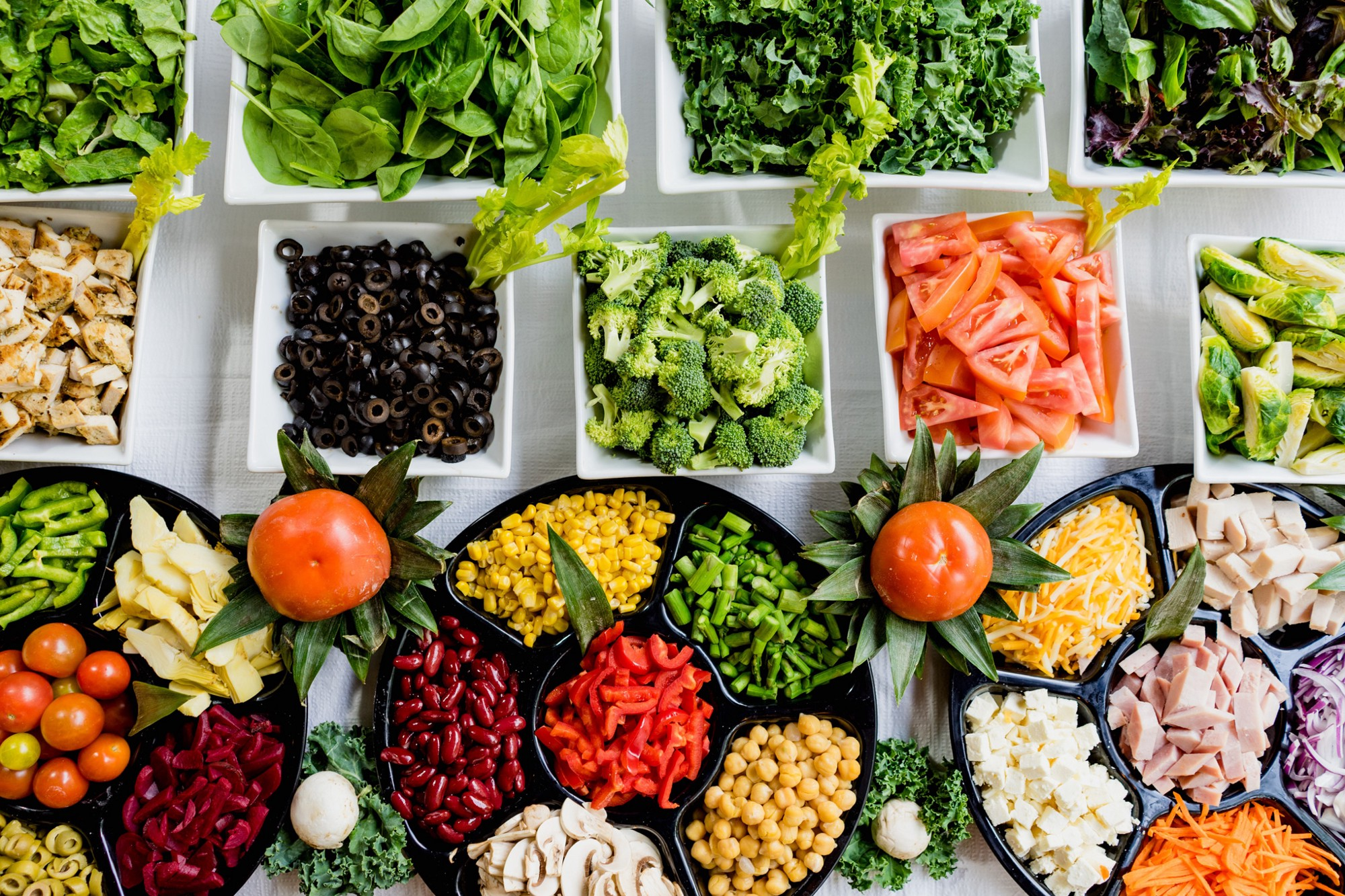 colorful salad bar with a wide variety of vegetables, meats, and cheeses