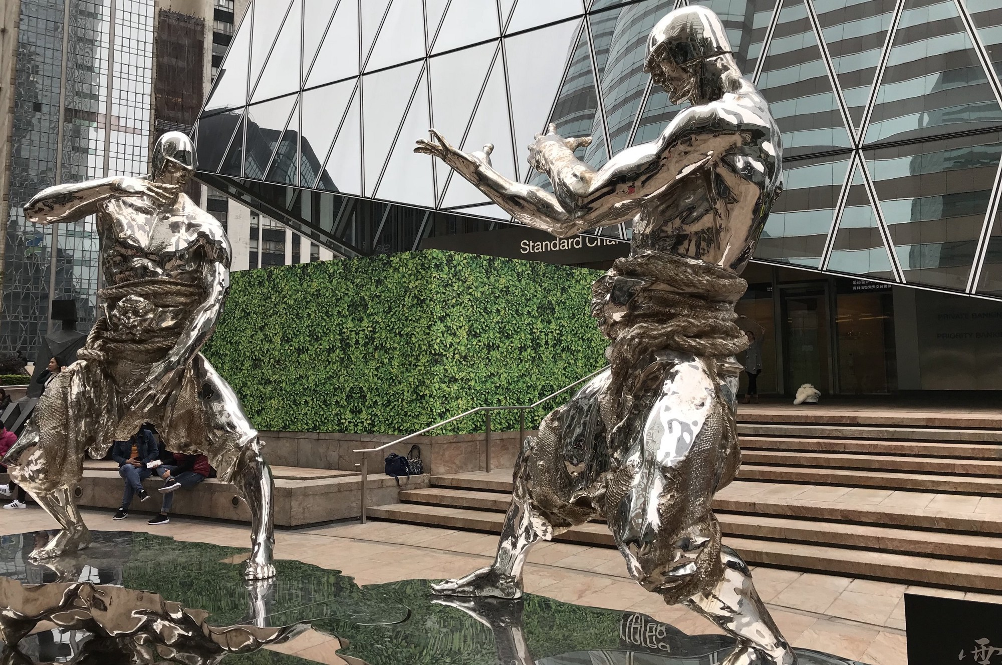 Pictured: Statues of two men in traditional martial arts poses facing one another, ready to fight. Photo taken in front of the Standard Chartered building, Forum, Hong Kong, Central.