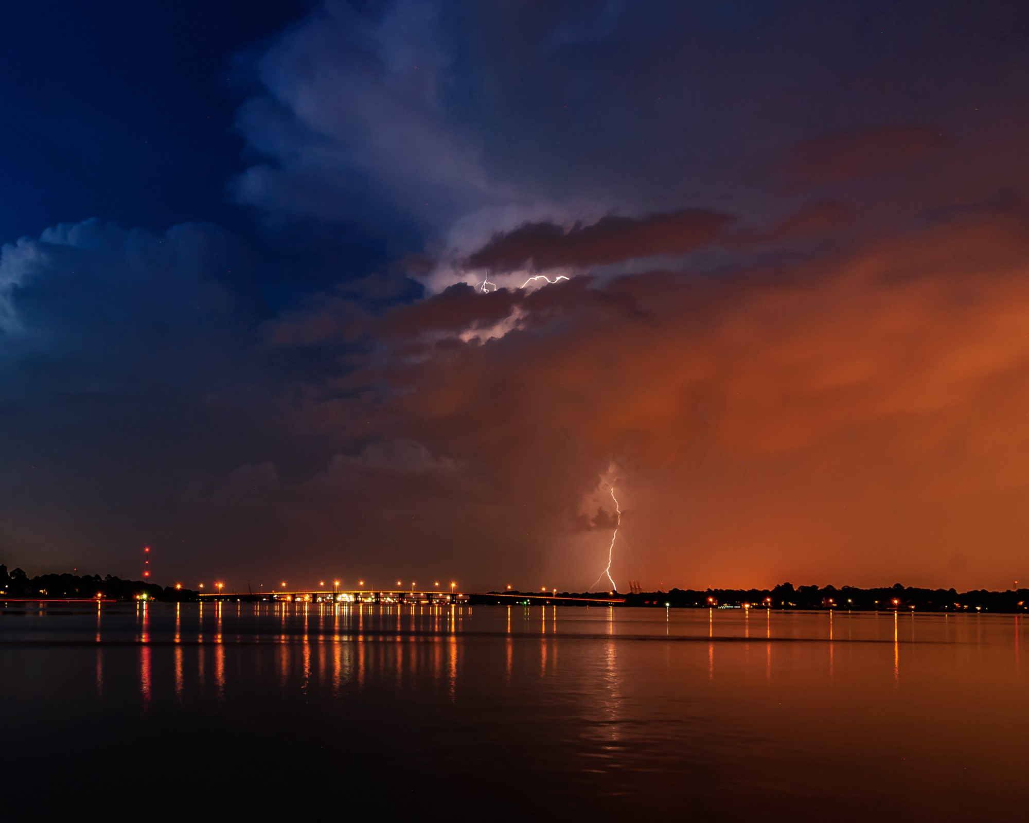 Lightening strikes light up the clouds above a body of water while lightening strikes the shore.