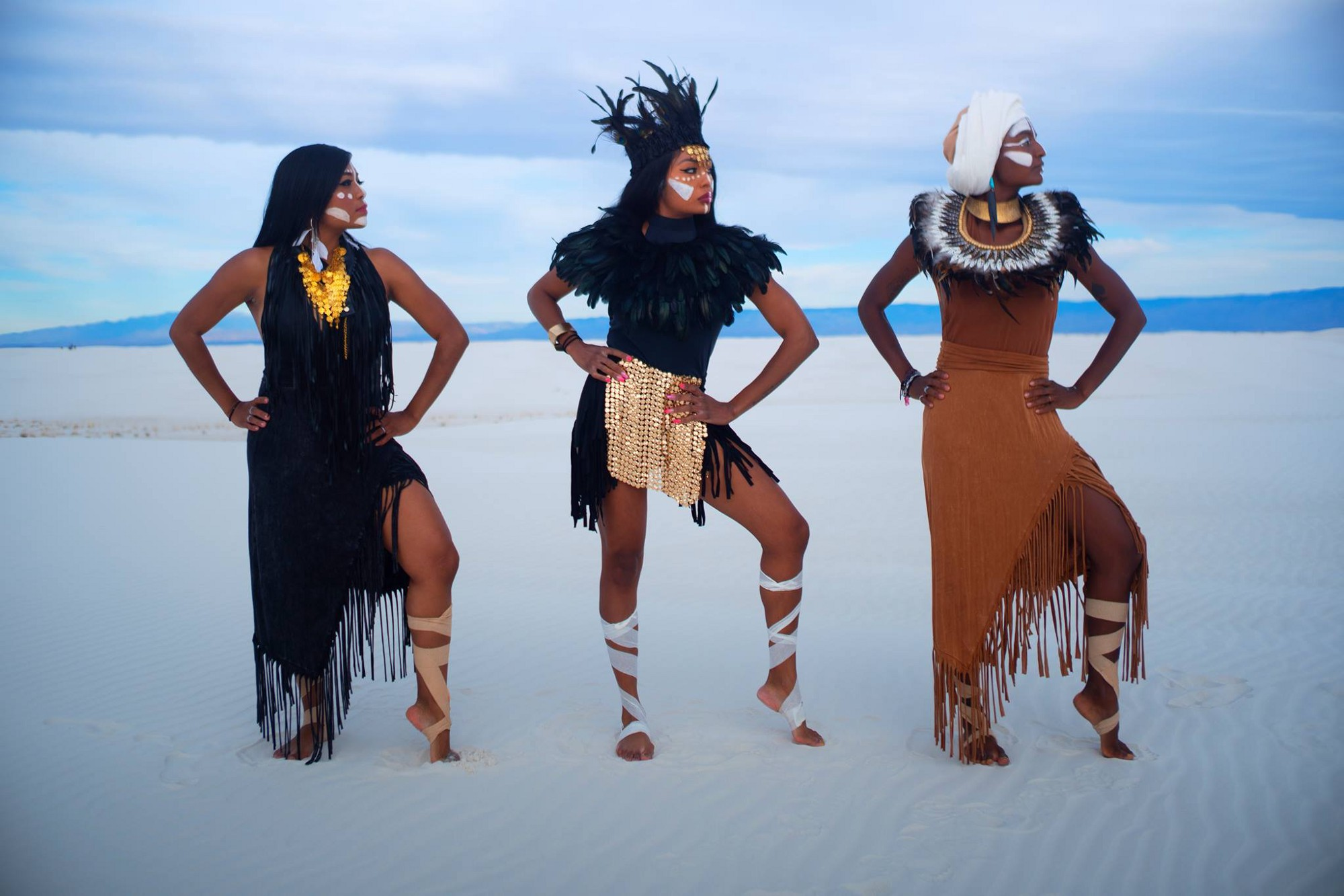 The three sisters pose in a glamorous mix of fringe, feathers, and gold jewelry with sand dunes and distant mountains behind them.
