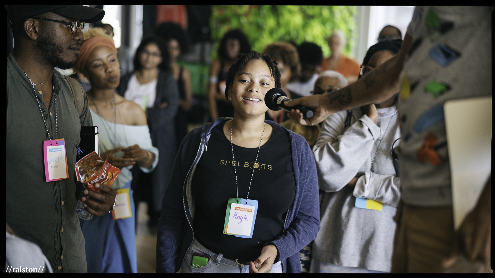 A young, smiling Black person is in a group being interviewed. The surrounding people wear badges that say Afrotectopia.