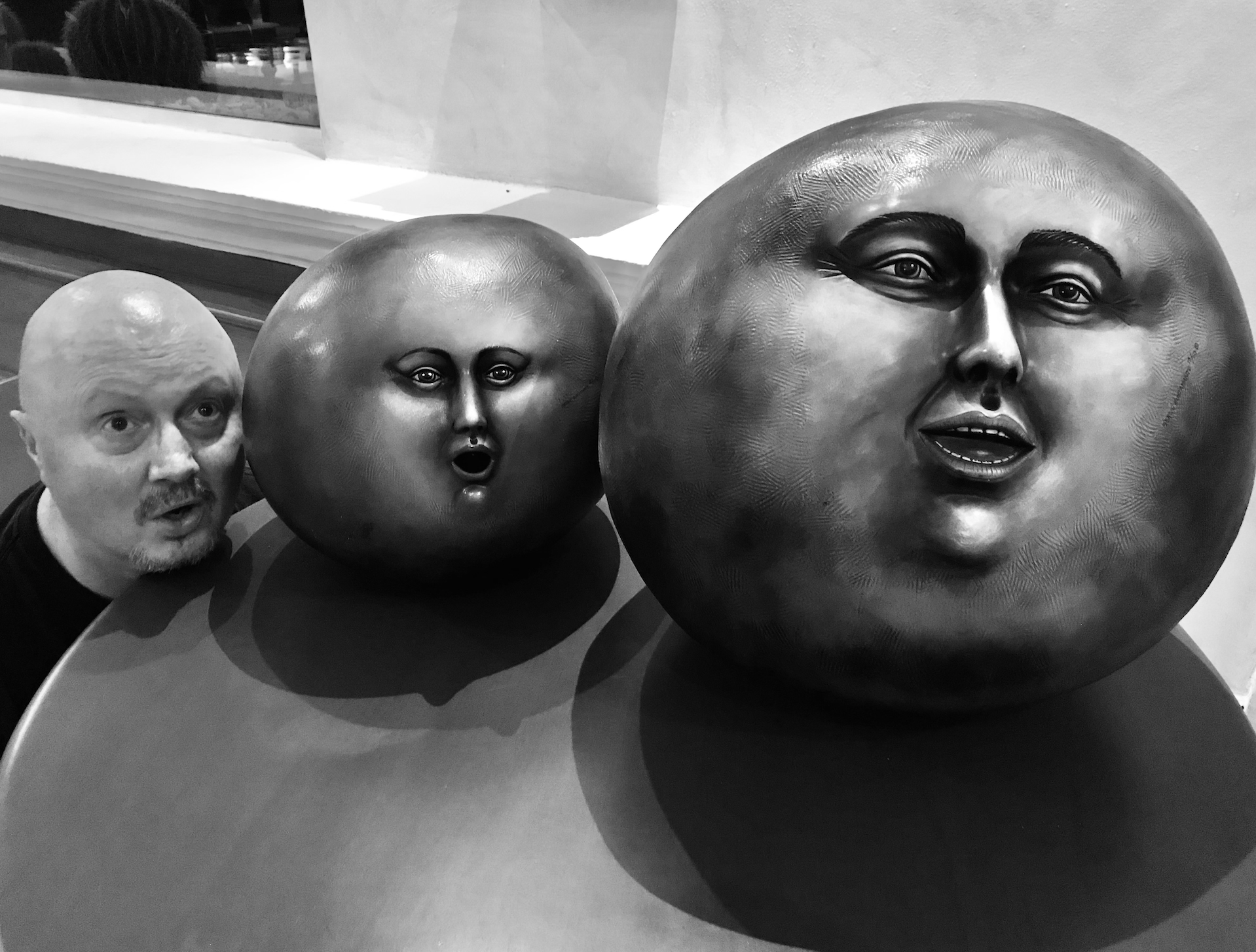 Me (with my bald head) in a black t-shirt bending down beside an end table with two different sized round balls with faces on them (modern art) in the main lobby at the Excellence Riviera Maya, Cancun, Mexico.