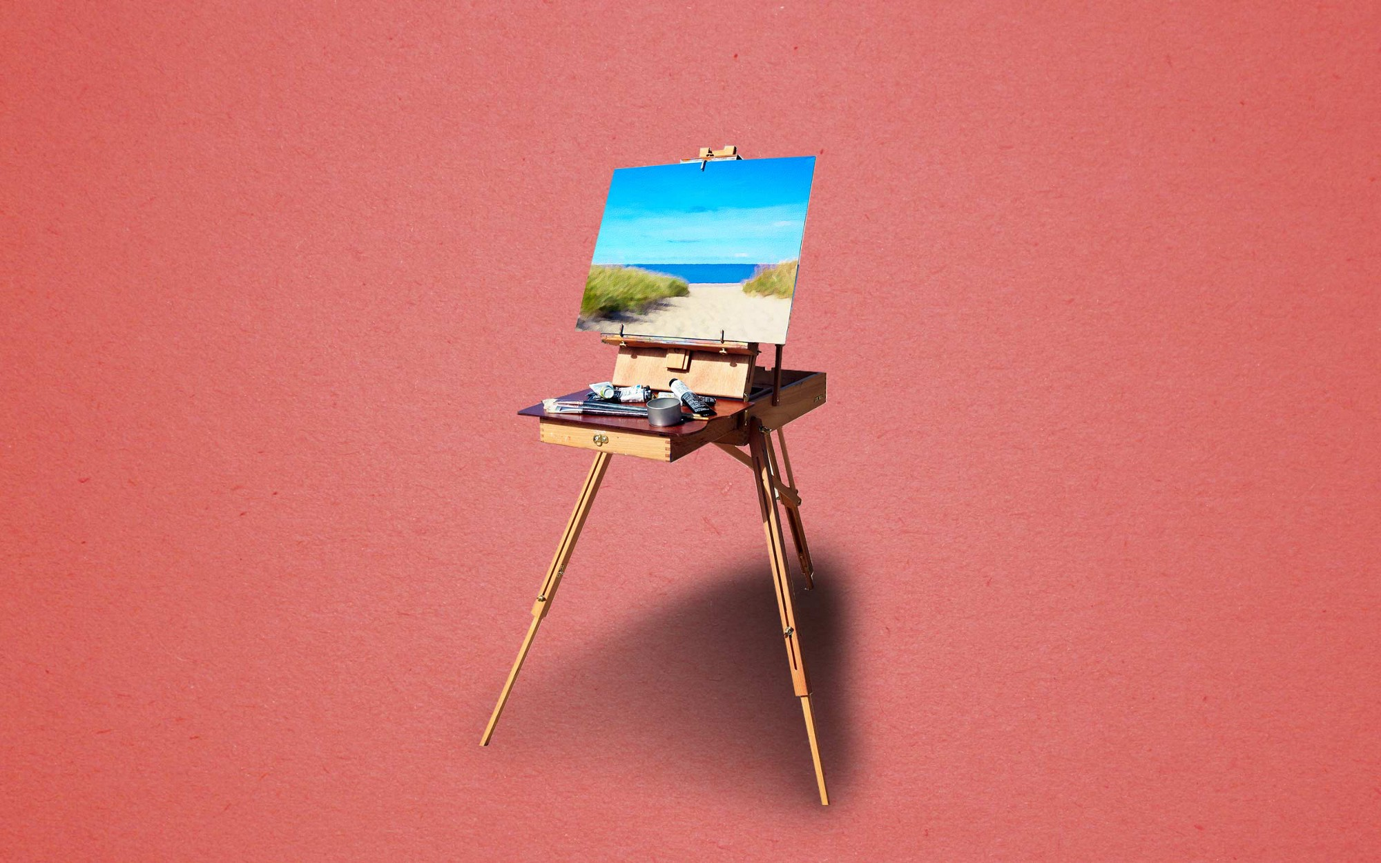 An image of a painting of a beach on an easel.