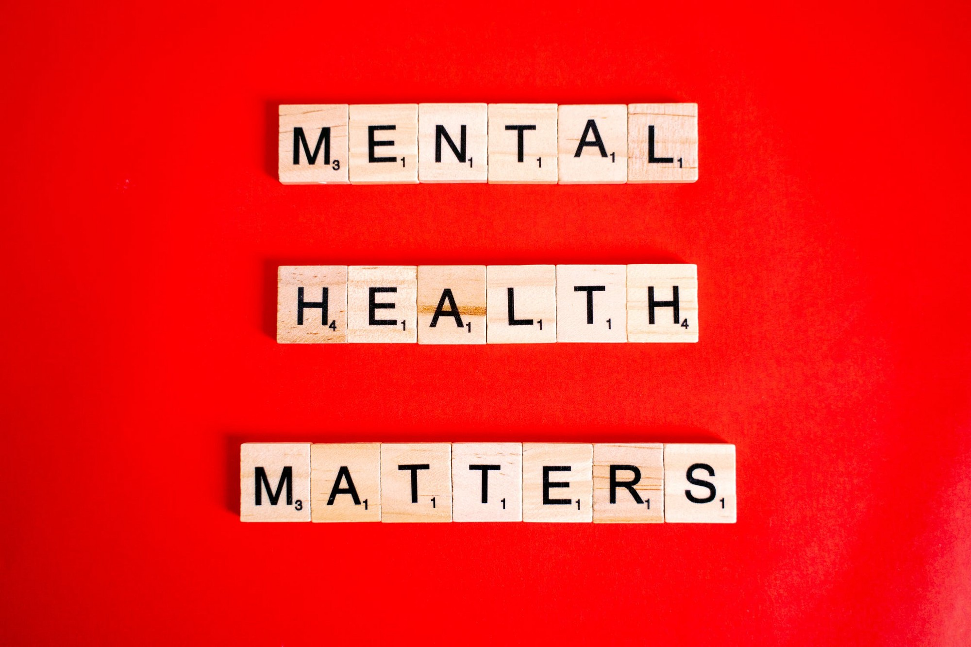 mental health matters written out in scrabble tiles against red background