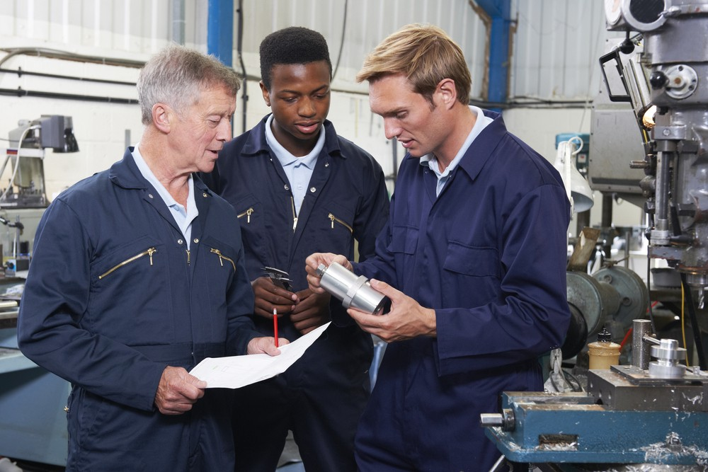 Image of three workers discussing about a piece of equipment