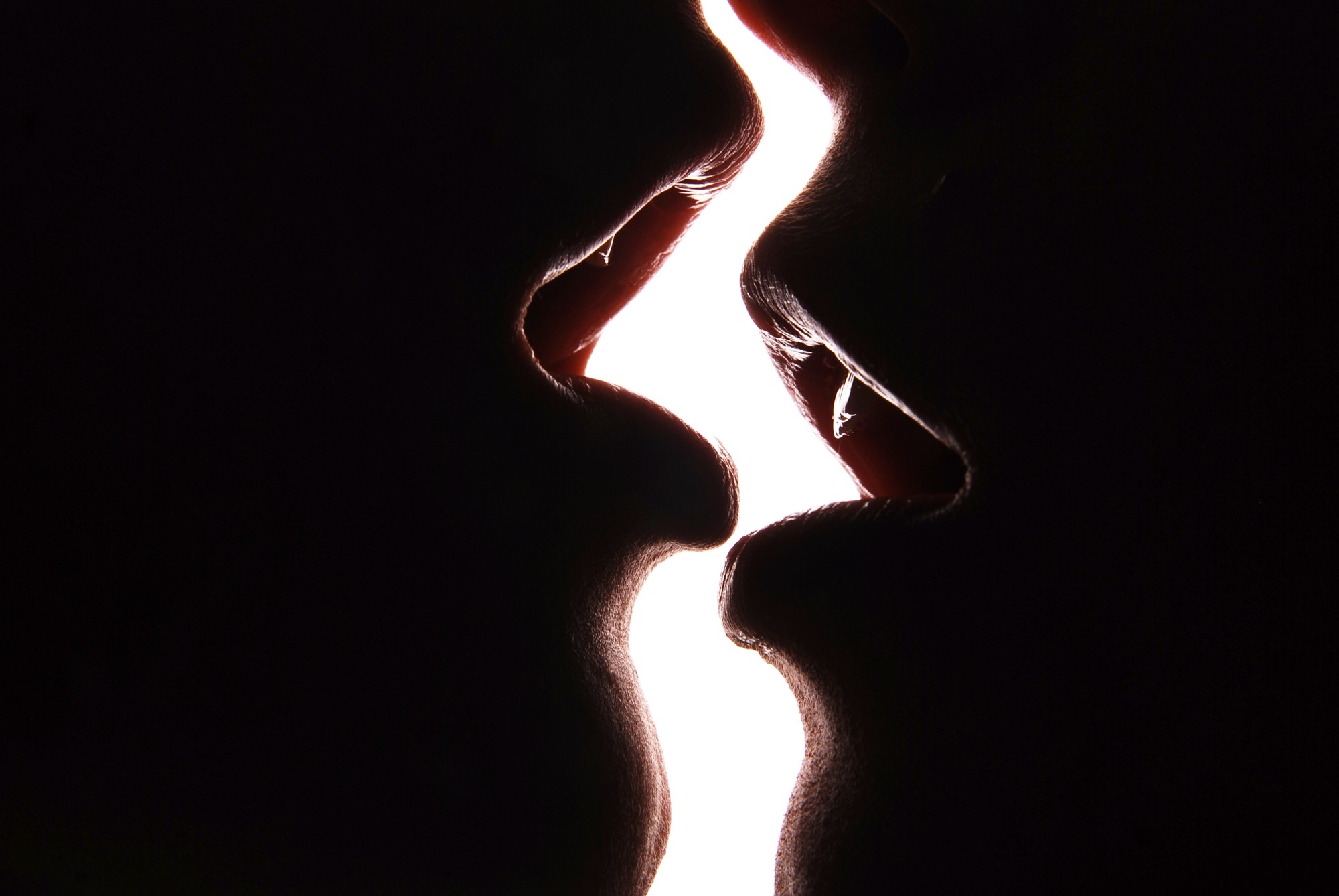 A close-up of a pair of mouths, almost touching. The are silhouetted black against a sliver of white background between them. Their lips are parted, hungry, wanting to touch but held back.