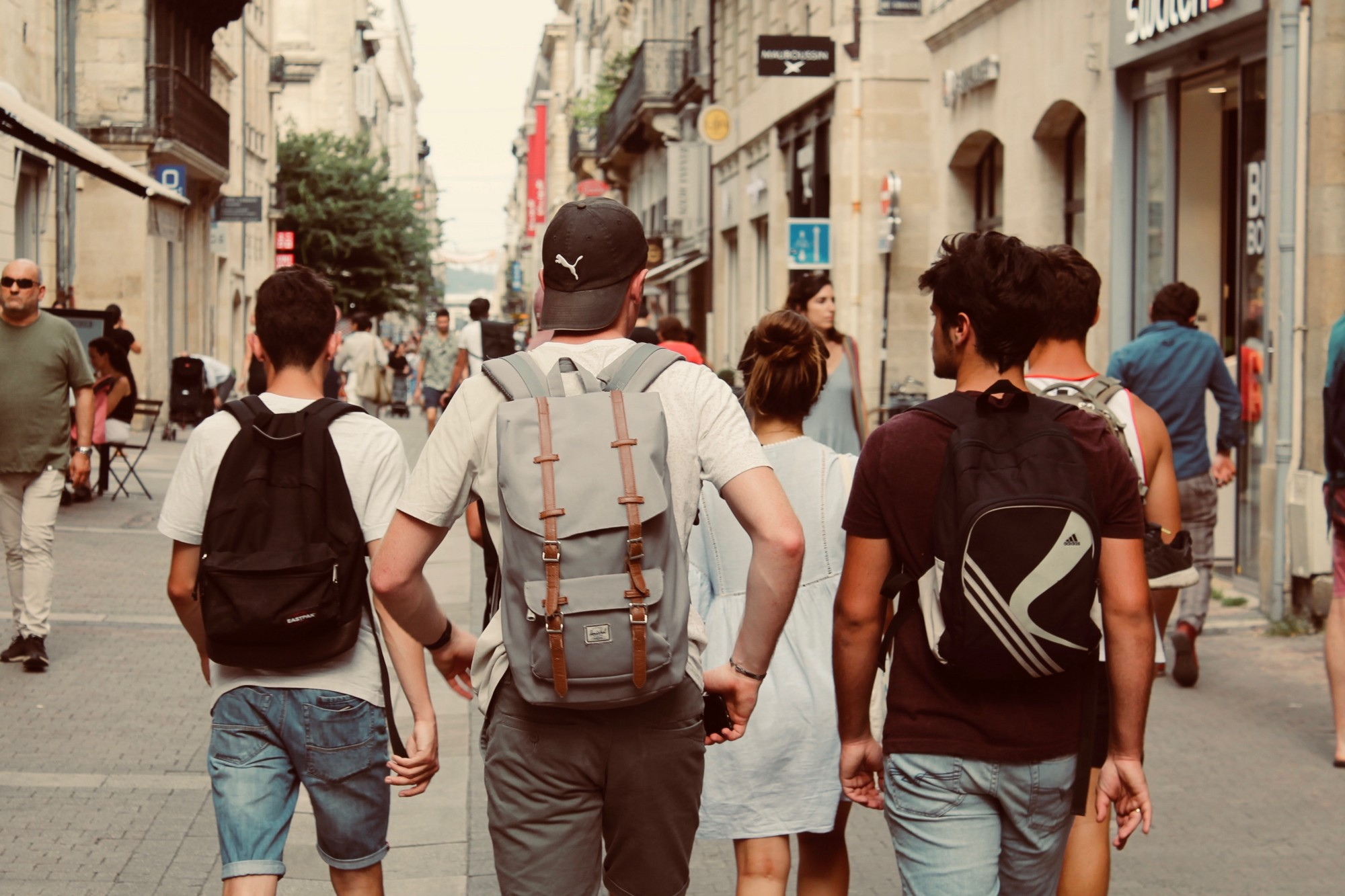 Teenagers walking down a street displaying various brand names on their bags and hats.