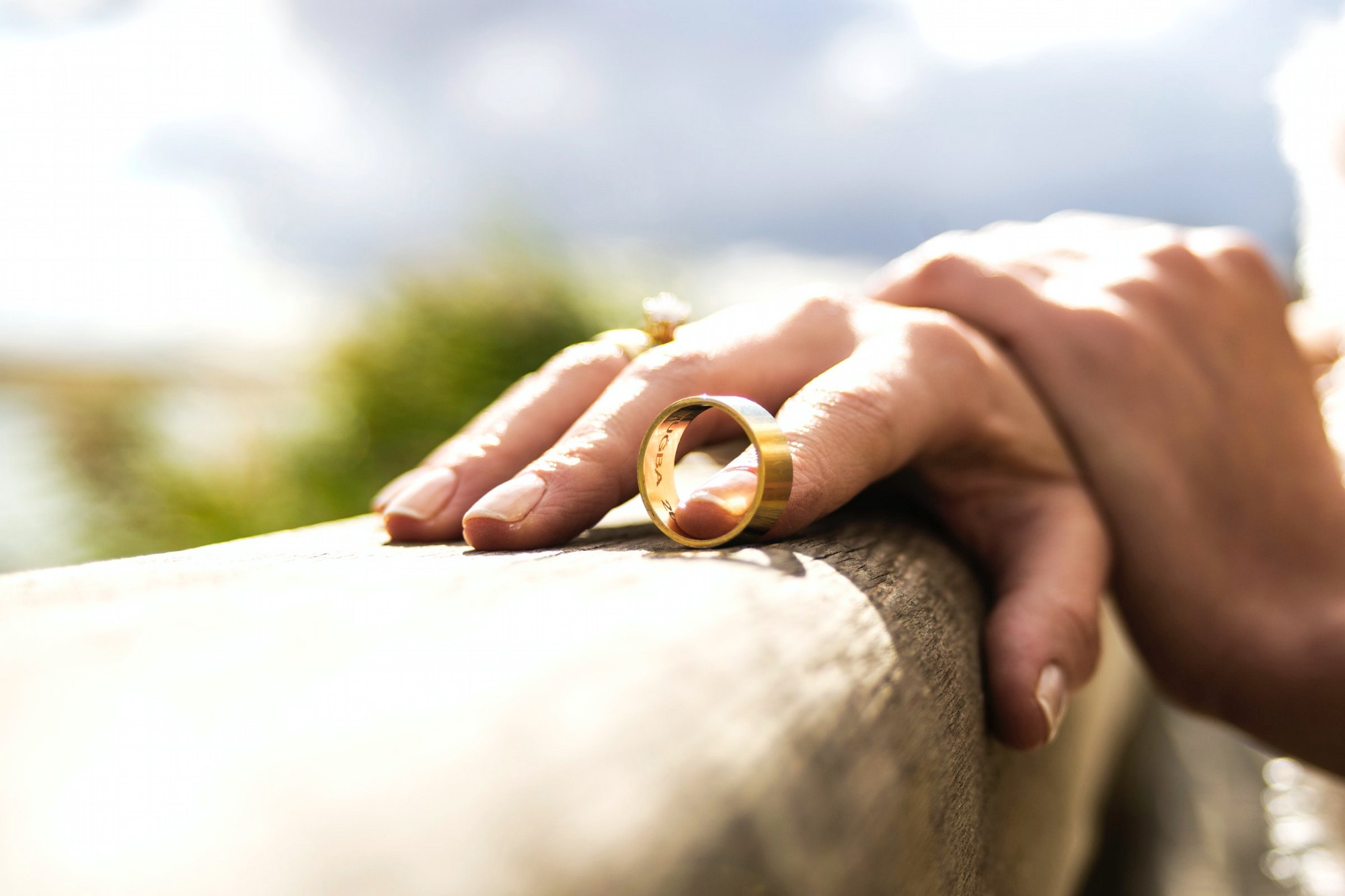 A hand resting on a wall. The tip of one finger is inside a wedding ring.