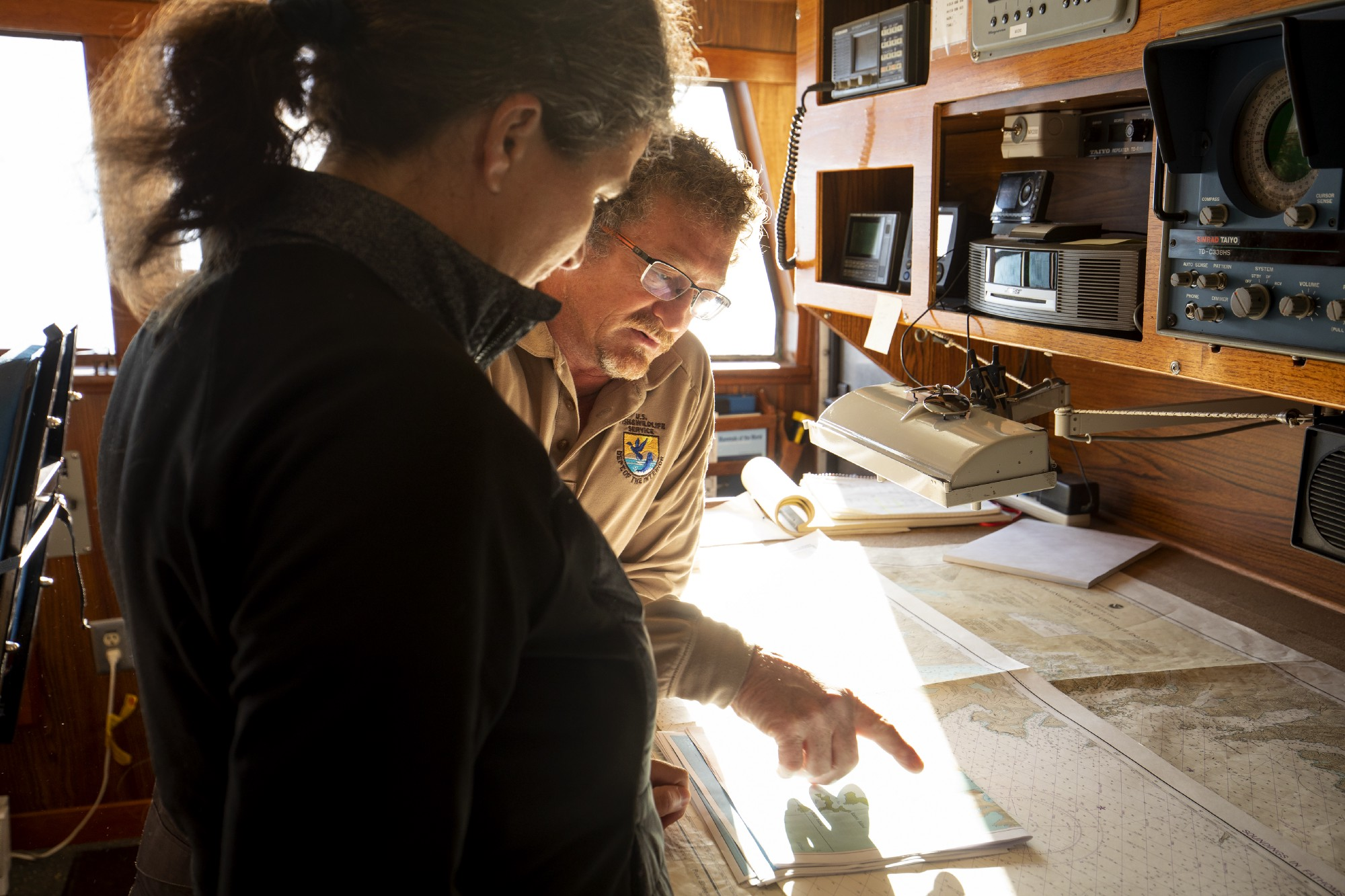 A man in brown uniform with USFWS logo and a woman in black jacket look at a maritime chart set out on a table in a ship's wheelhouse.
