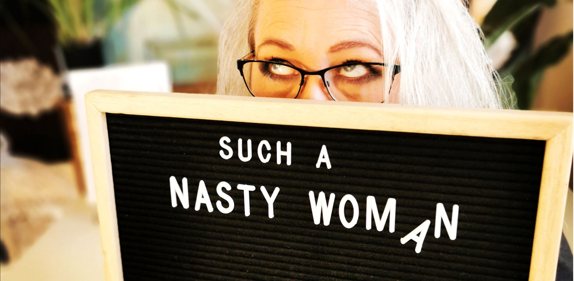 """Author holds sign board that reads """"Such a nasty woman."""" She is rolling her eyes."""