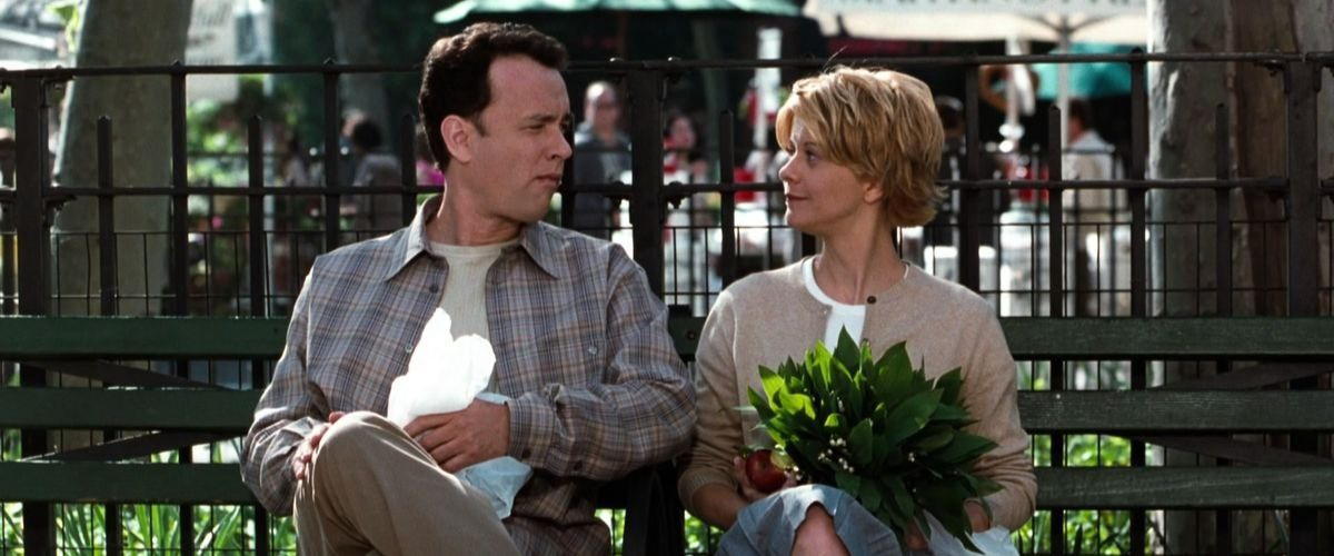 Still of You've Got Mail with Tom Hanks and Meg Ryan holding plants on a park bench in New York City