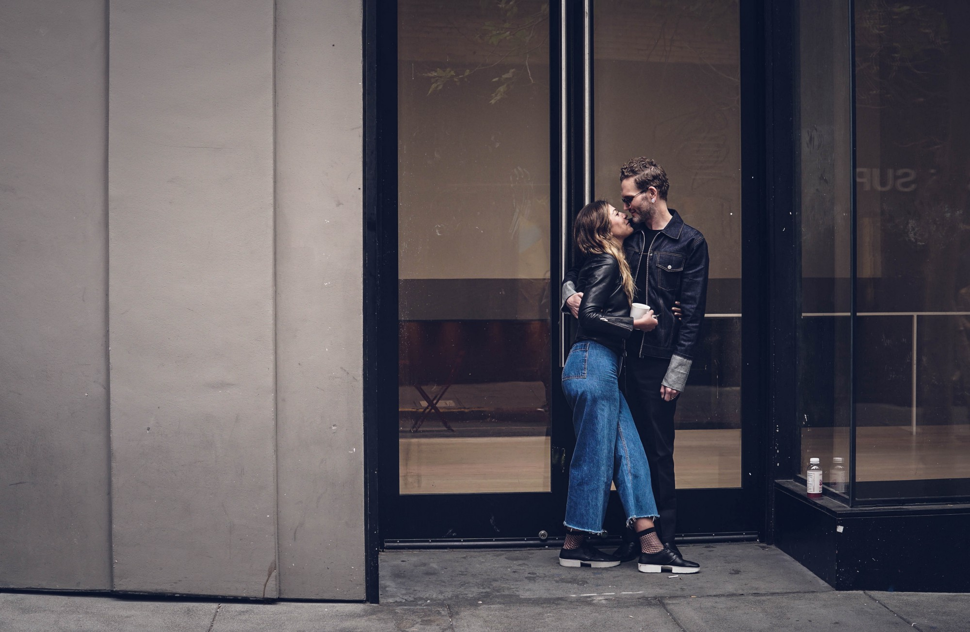 Couple about to kiss in the doorway outside a building